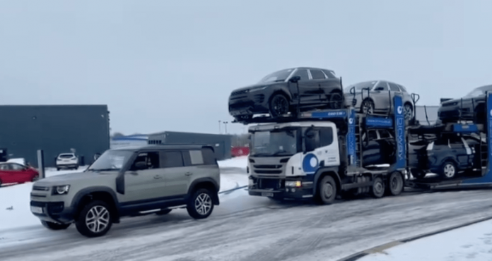 Land Rover Defender rescues a car transporter stuck in the snow