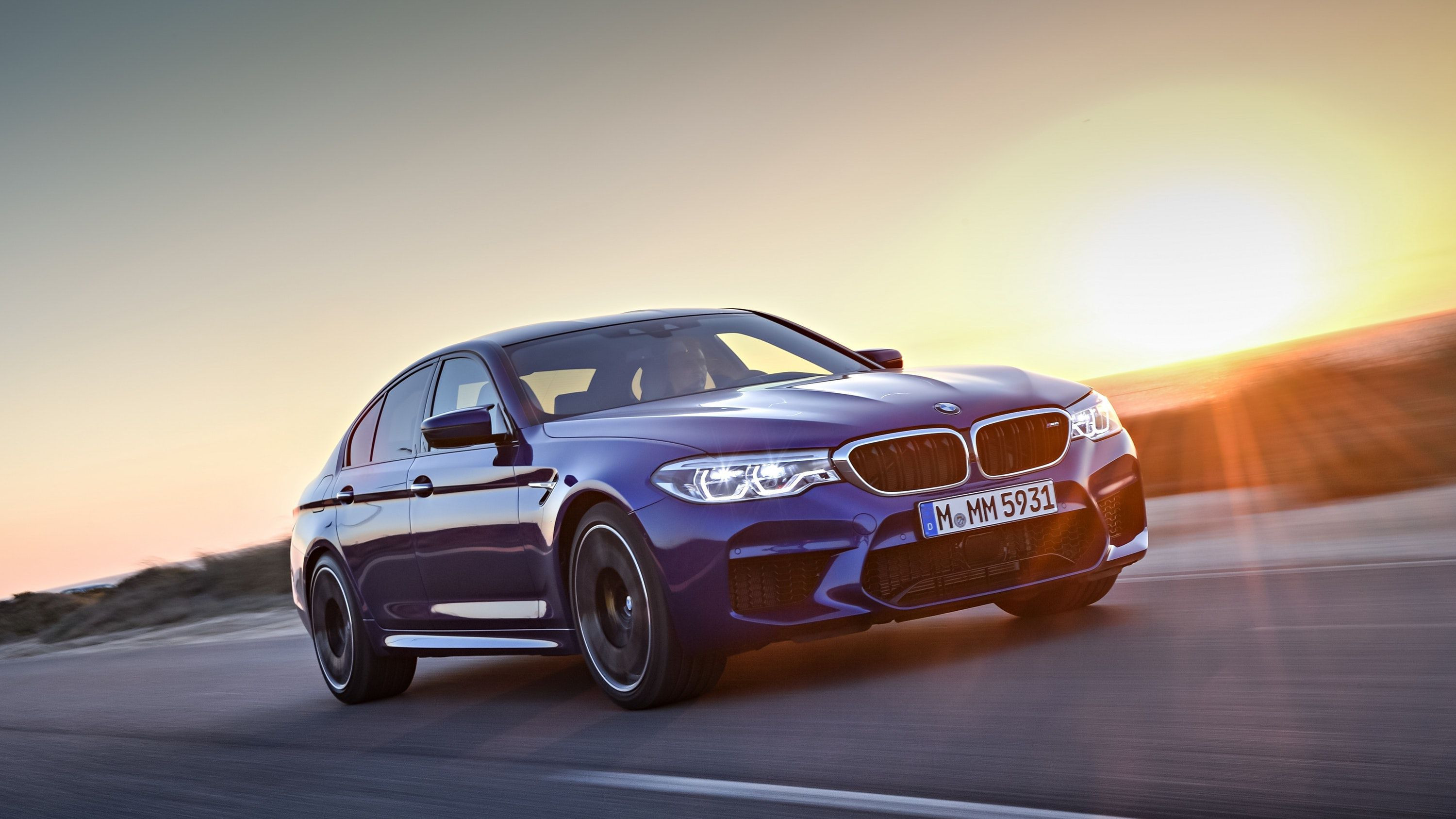Blue BMW M5 driving at sunset