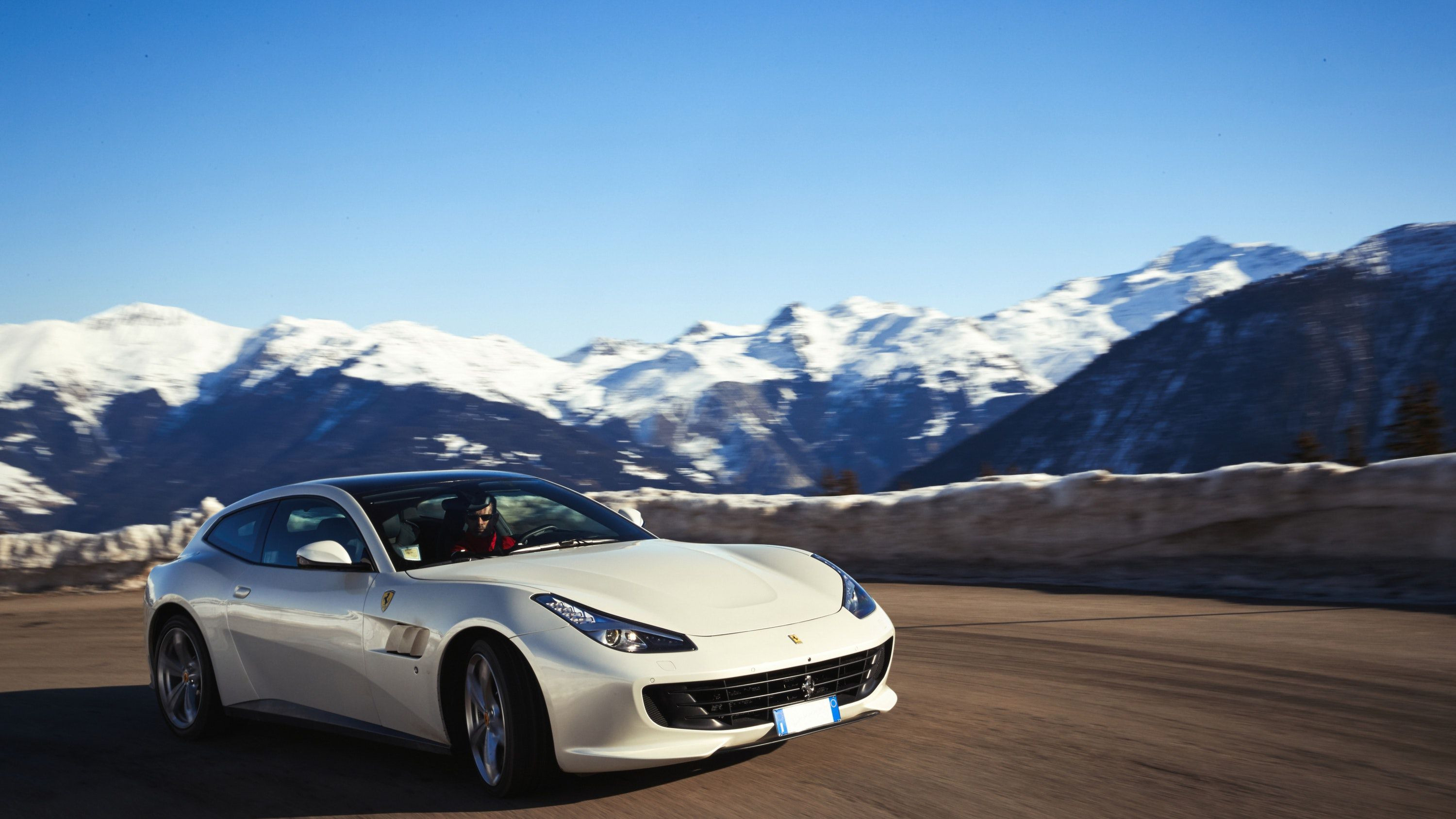 White Ferrari GTC4 drving along a road in the winter with snow on the mountains