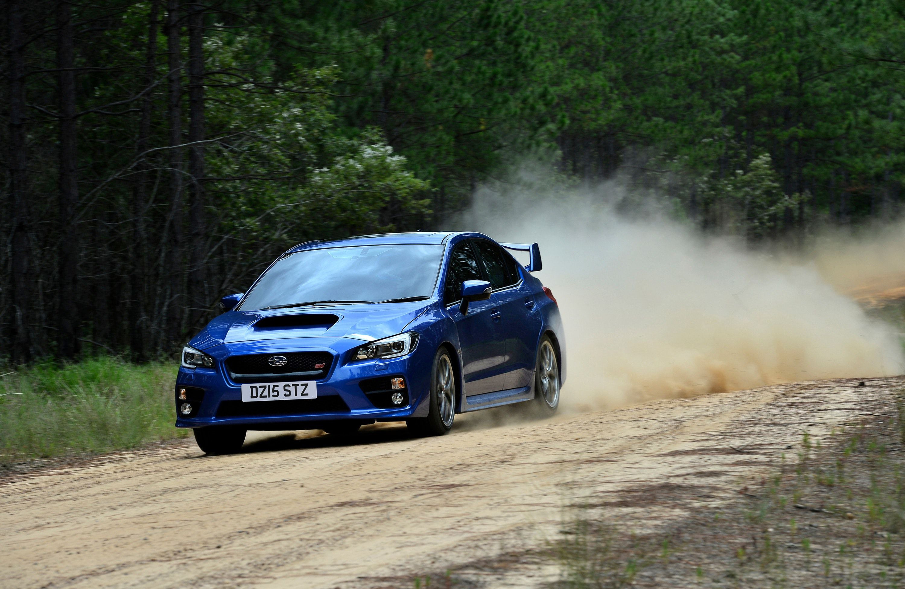 Subaru driving on a dirt track through a wooded area