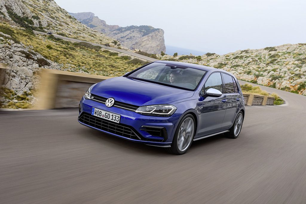 Blue Golf R driving toward the camera on a winding road with mountains and a sea view in the background