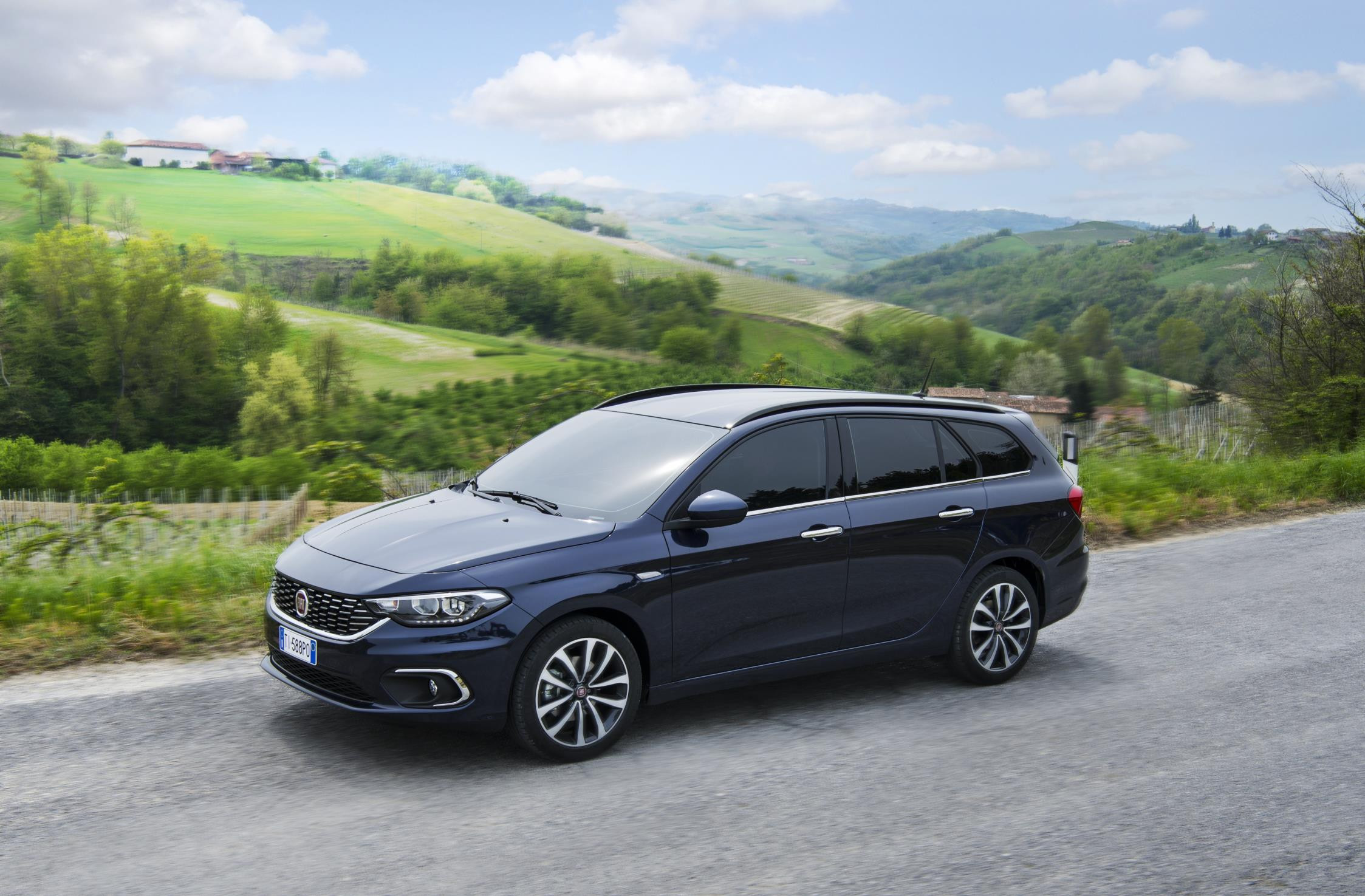 Blue Fiat Tipo Station Wagon driving through sunny countryside