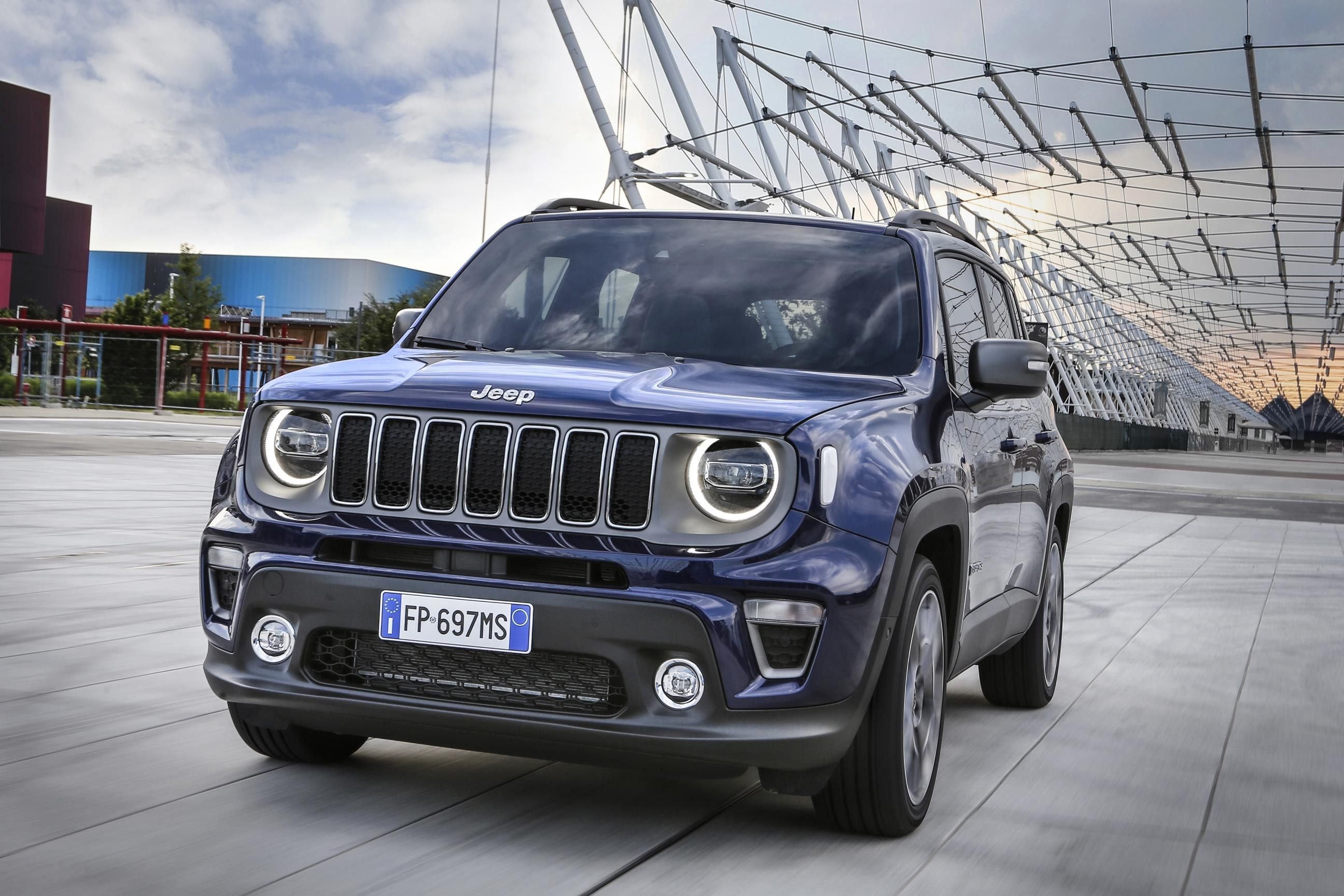 Blue Jeep Renegade parked with sculptural building behind it