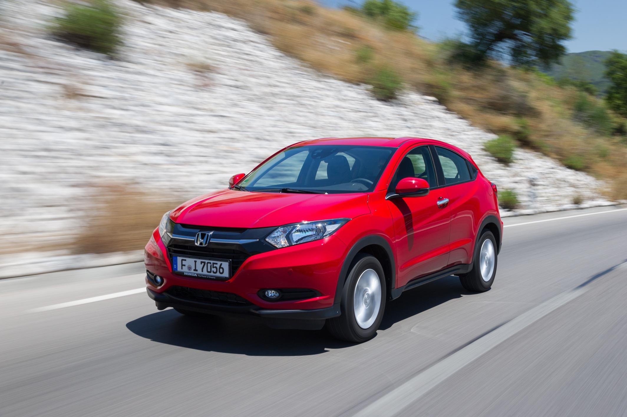 Red HOnda HR-V driving quickly down a road towards you