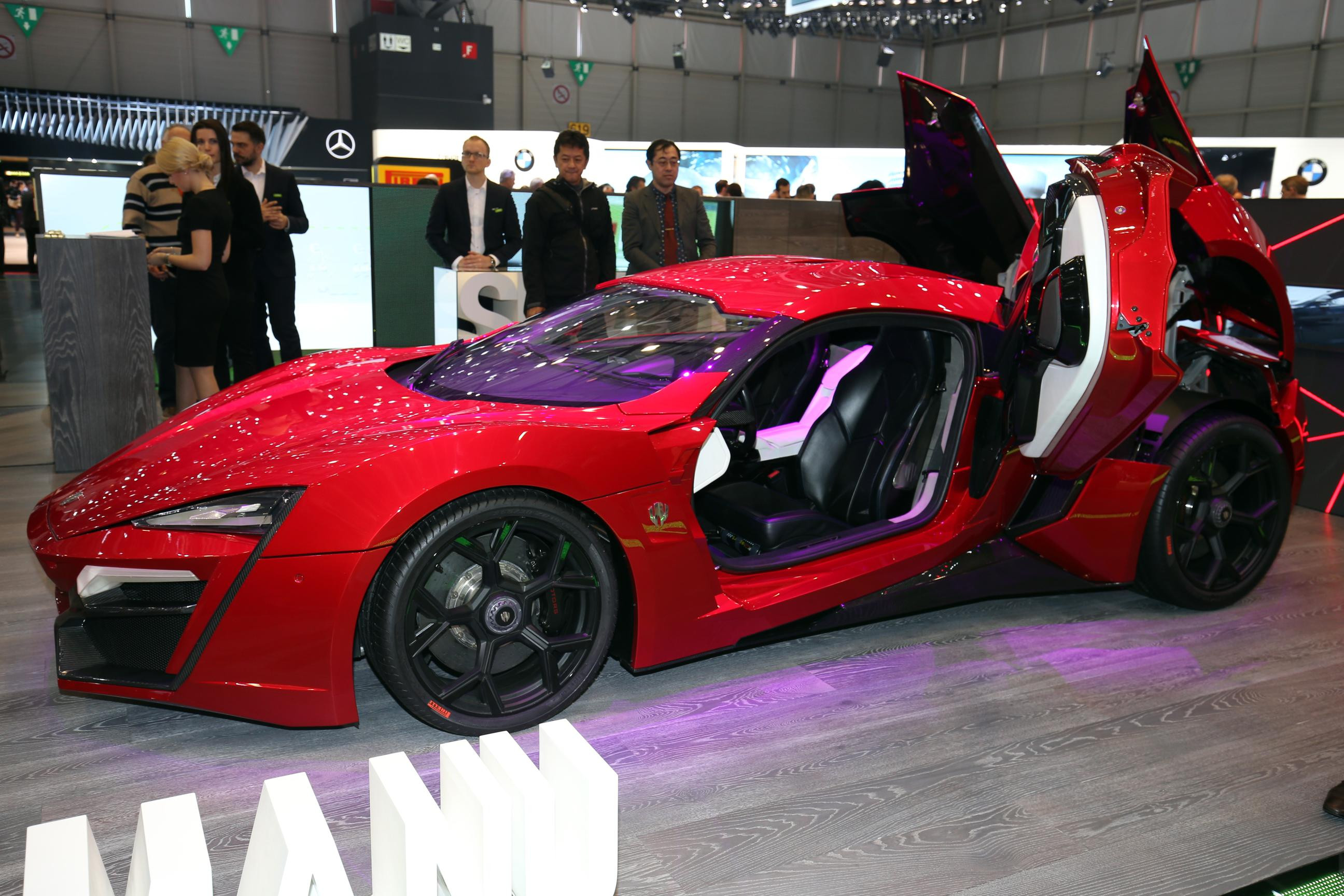 A red Lykan Hypersport, facing left with scissor door open to reveal black and white leather interior.