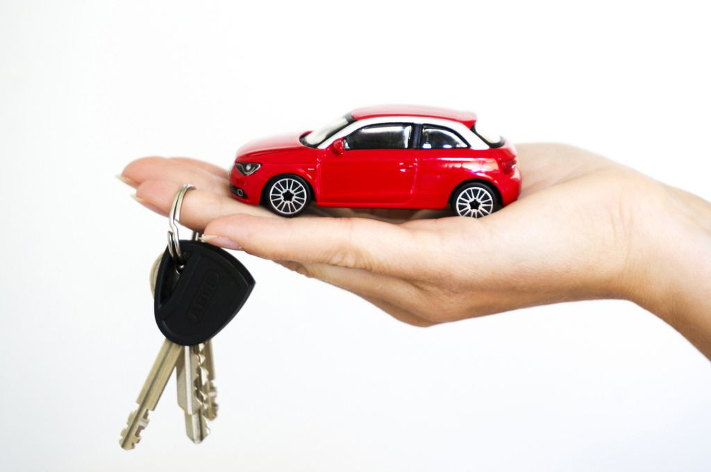Red toy Audi A1 in a hand with car keys dangling from it