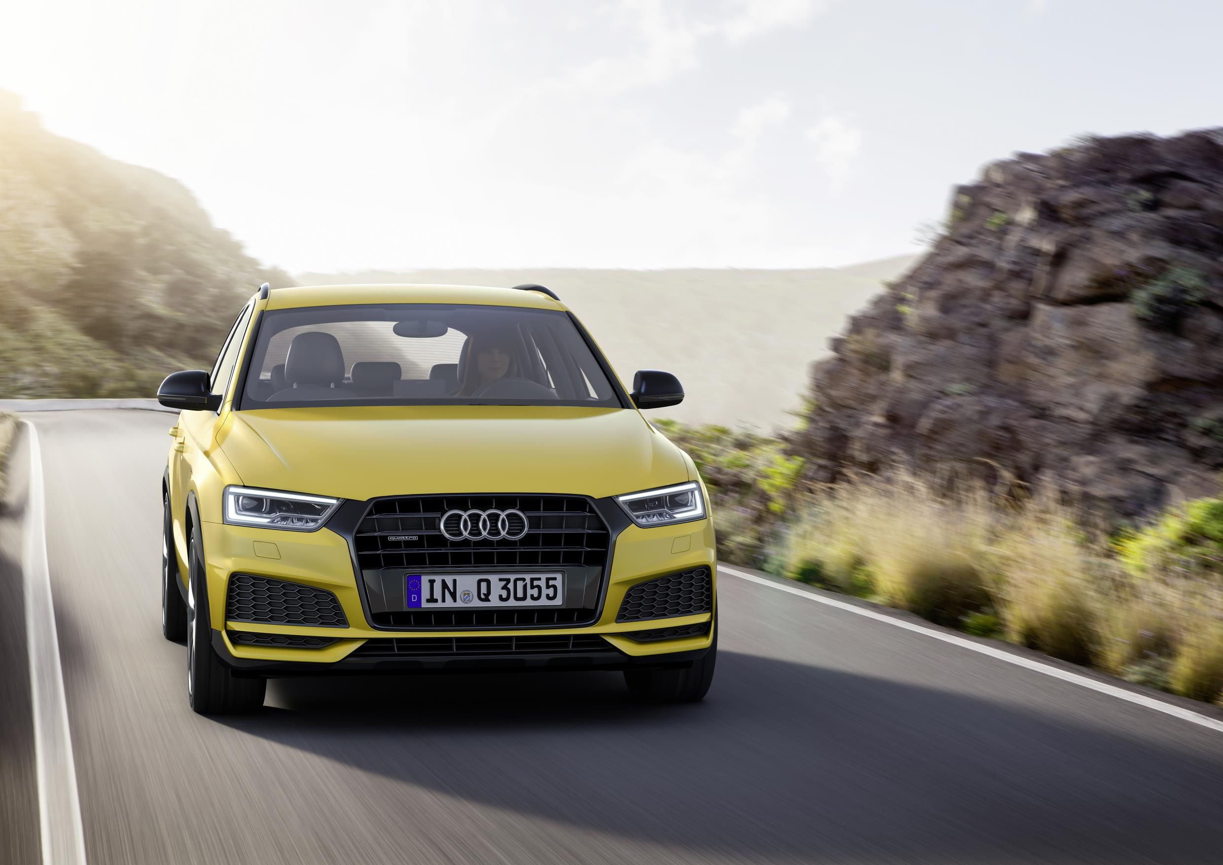 Yellow Audi Q3 driving towards you on amazing road