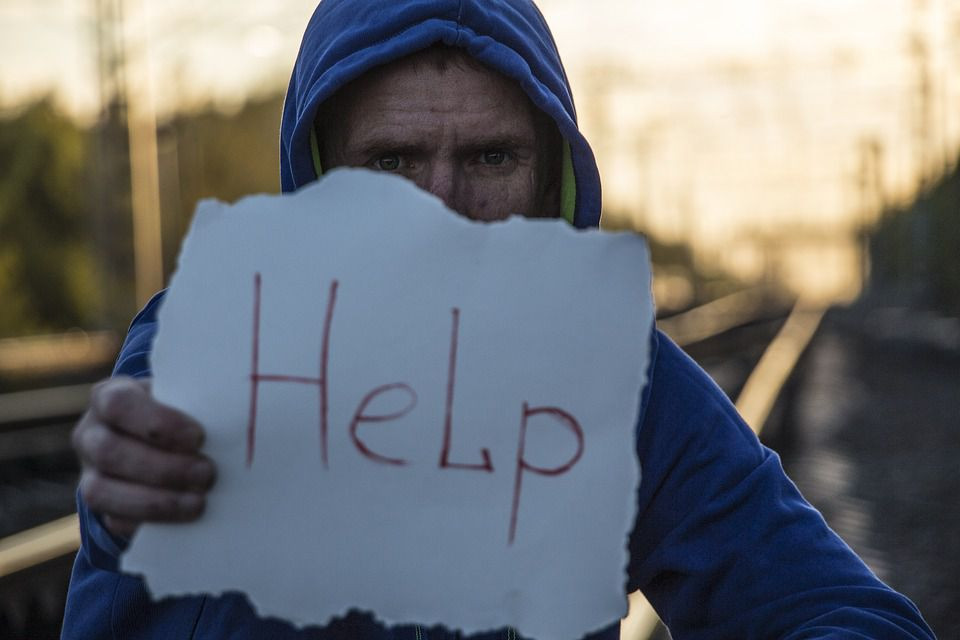 Man in a blue hoodie standing by the road with a sign saying help