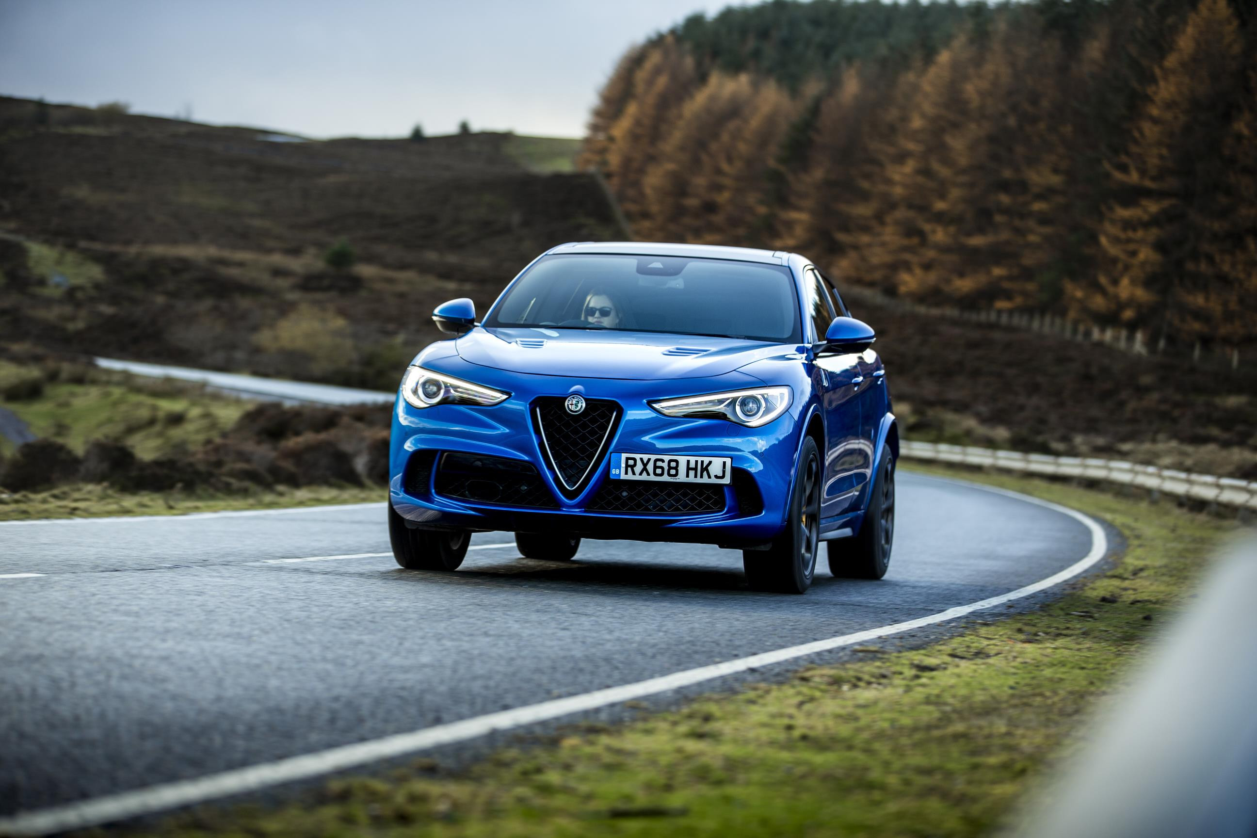 Bright blue metallic Alfa Romeo Stelvio Quadrifoglio driving towards you