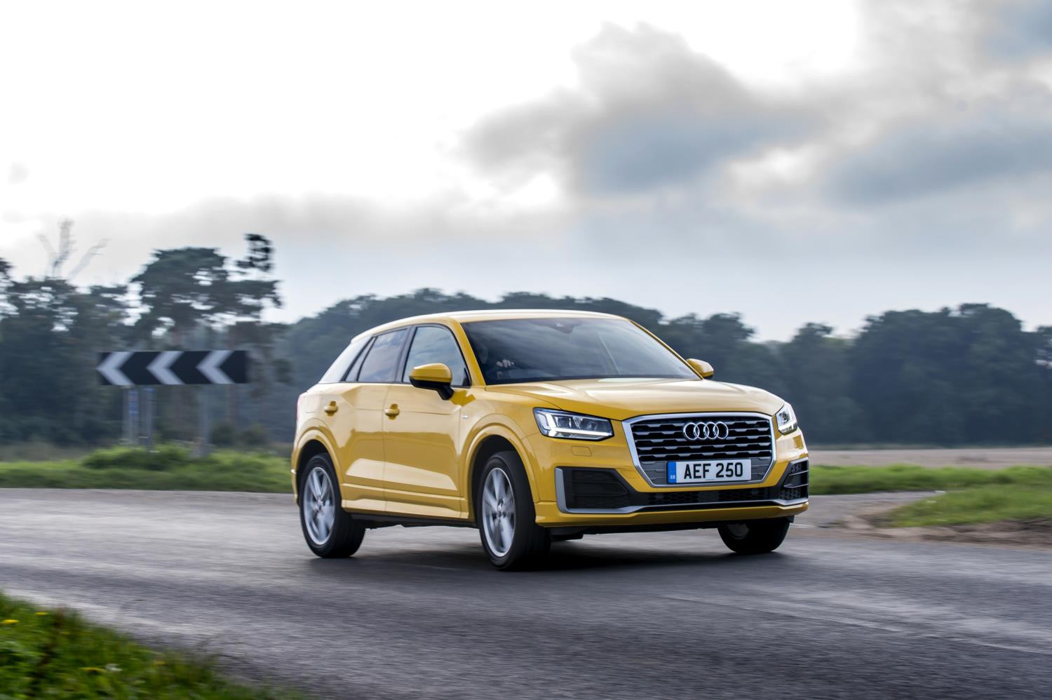 Bright yellow Audi Q2 driving down the road towards you