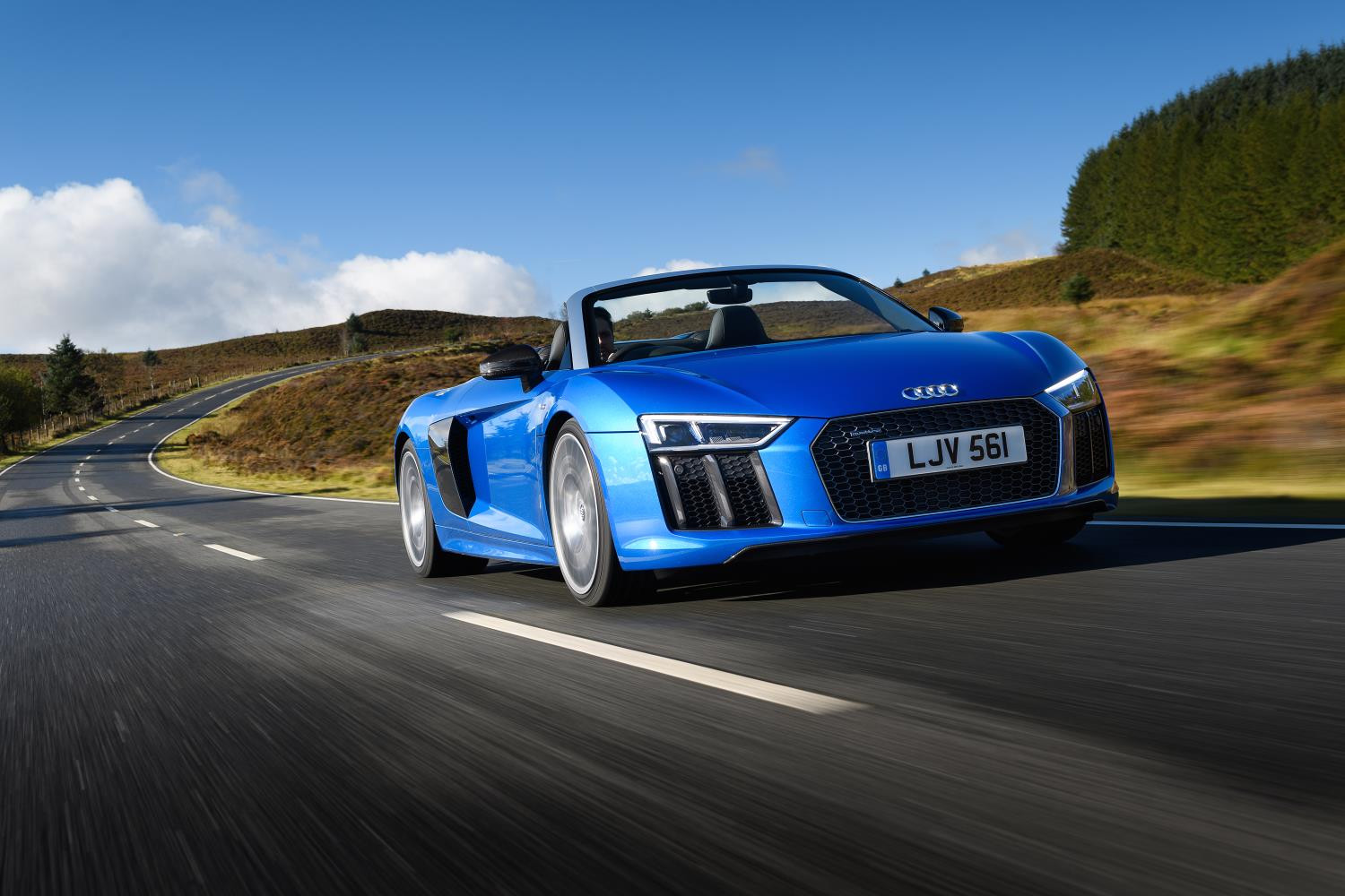 Bright blue metallic Audi R8 spyder whizzing along a country lane