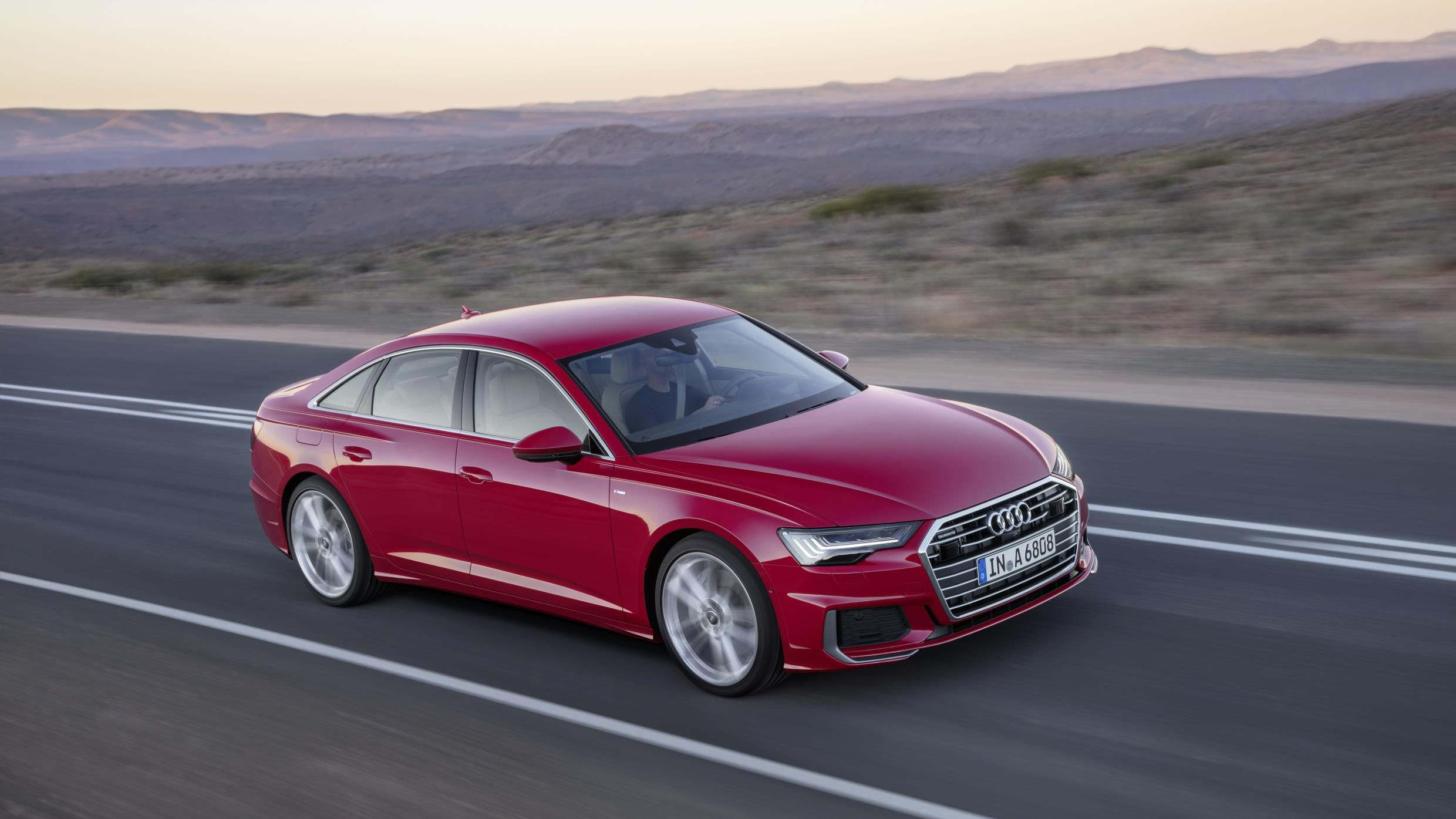 Red Audi A6 driving side on through a desert