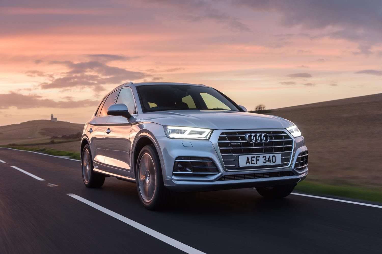 SIlver Audi Q5 driving towards you at sunset down an empty road
