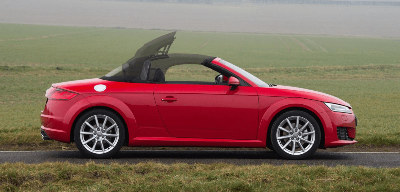 Red Audi TT roadster parked side on with roof going down