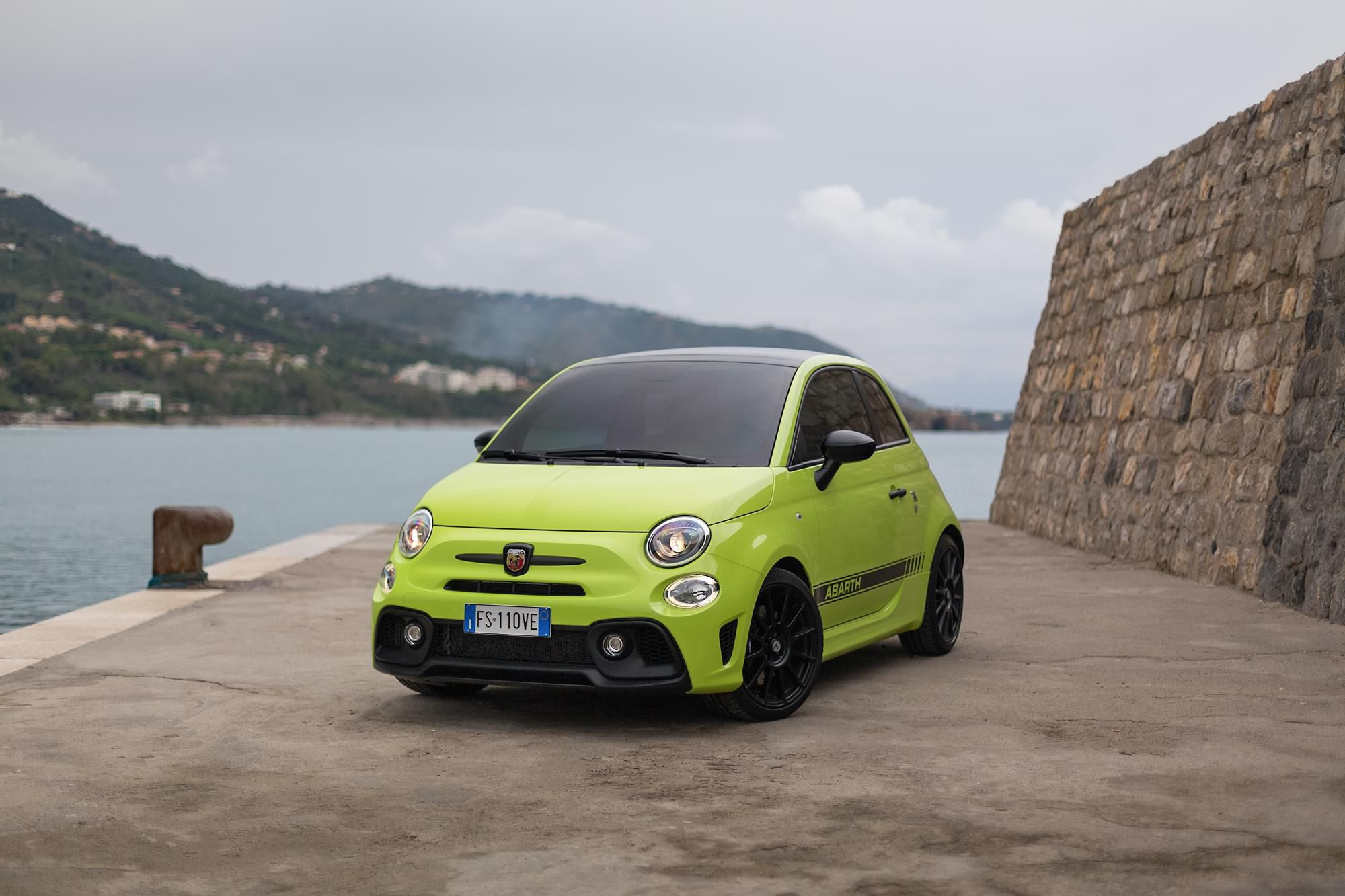Lime green Abarth 595 Competizione parked two thirds wide on by a dock