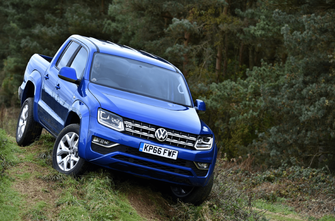 Blue Volkswagen Amarok off-road on difficult terrain