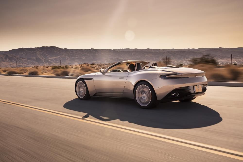 Aston Martin DB11 Volante driving away from you at dusk