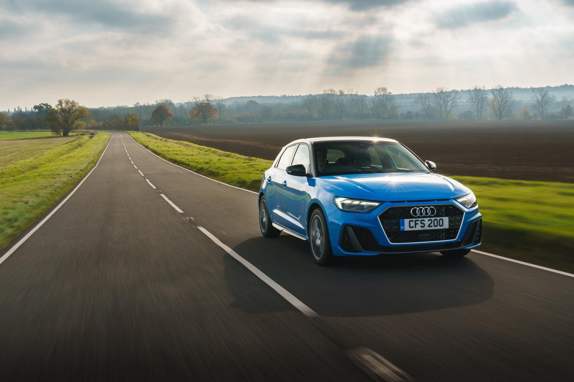 Bright blue Audi A1 driving toward you on a country road