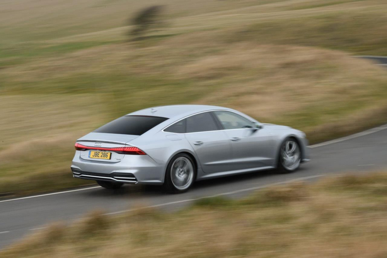 Silver Audi A7 driving at speed on a country lane seen from the side