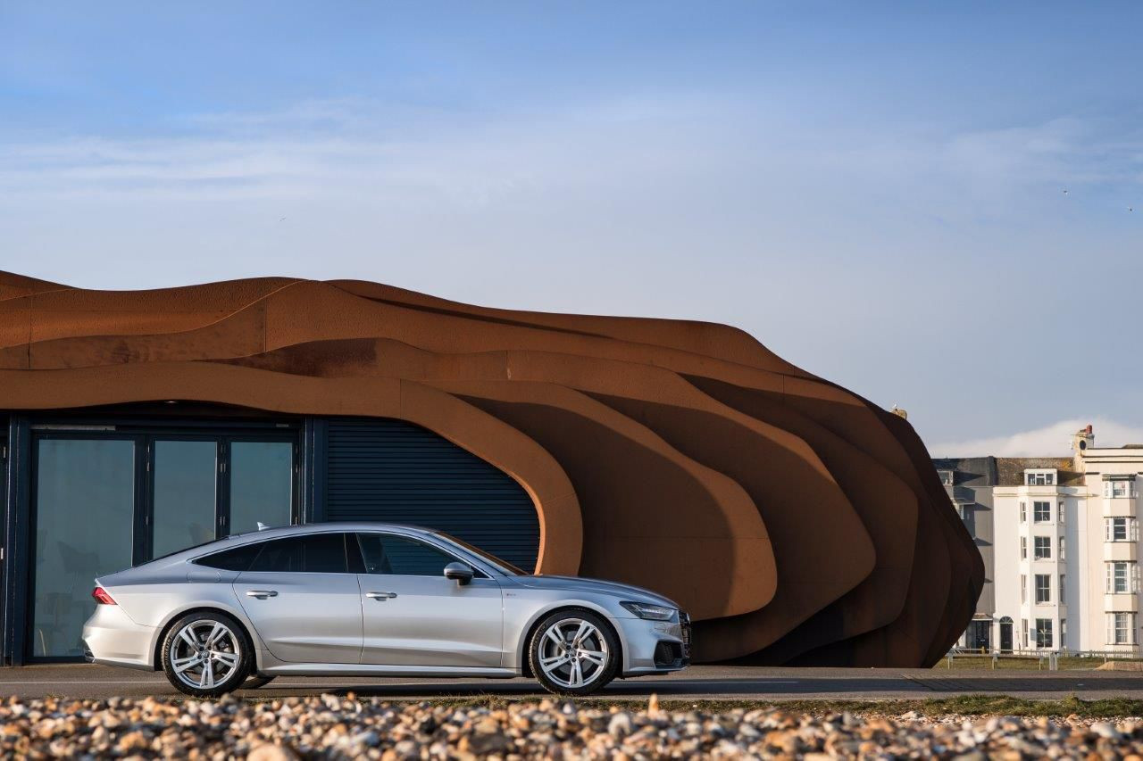 Silver Audi A7 side on outside a building which looks like a cave
