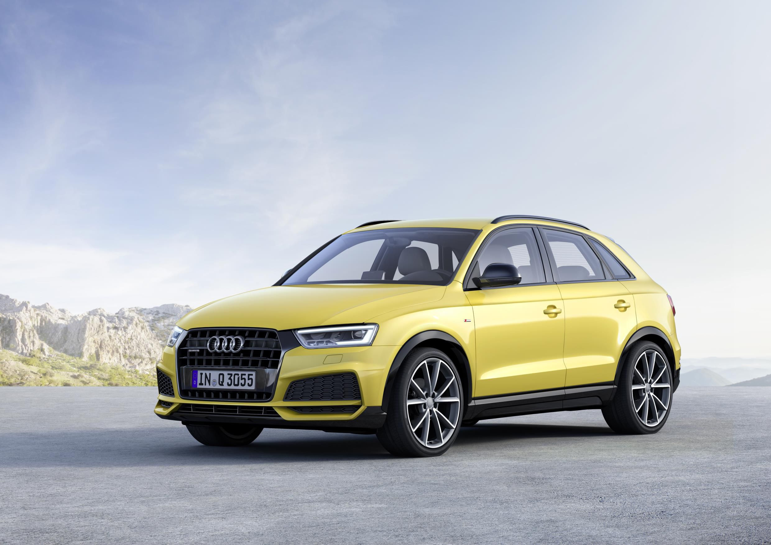 Yellow Audi Q3 two thirds side on with mountain and sky backdrop