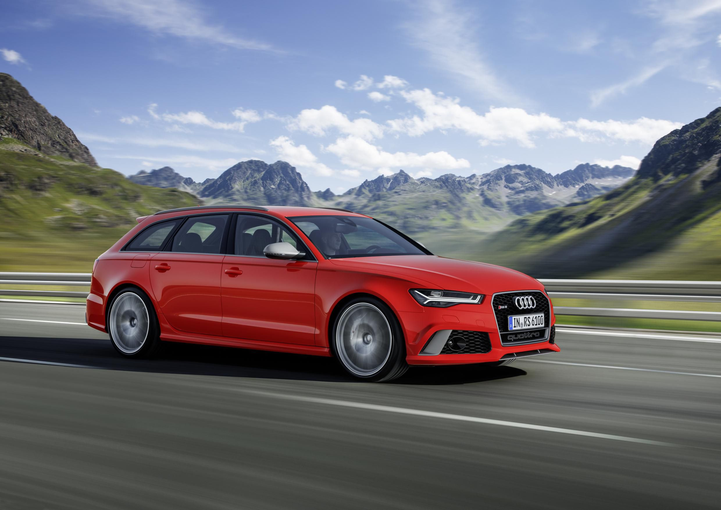 Red Audi RS 6 moving at speed through mountain roads