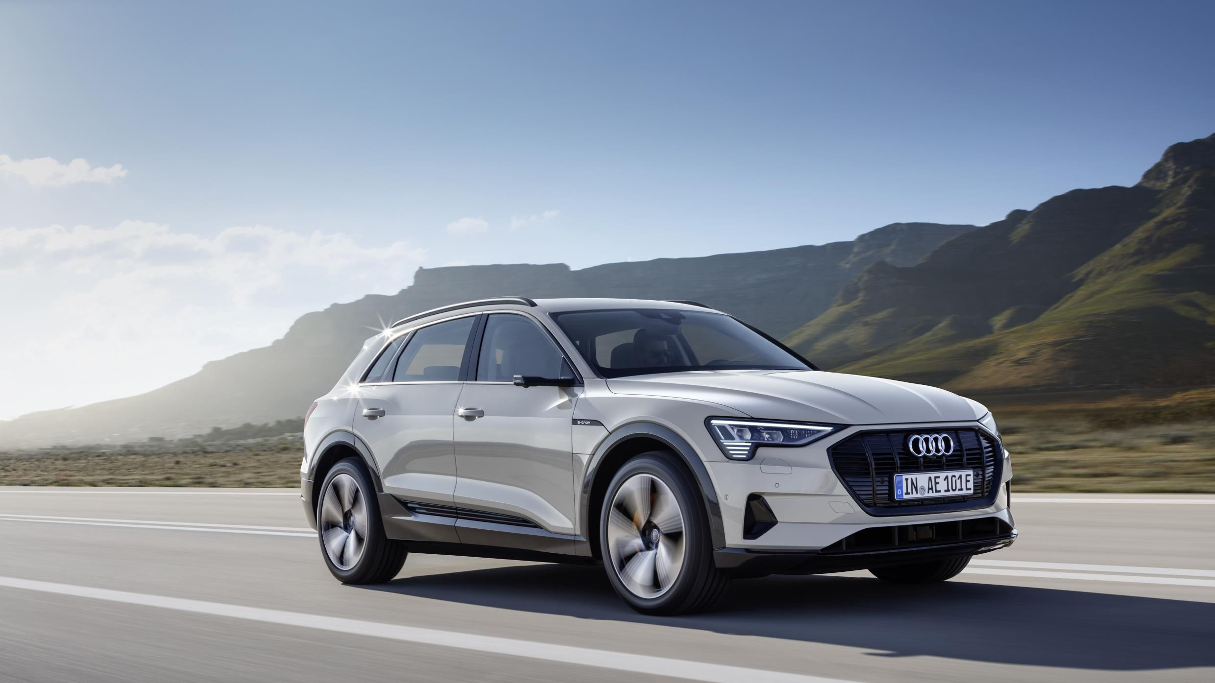 Silver Audi e-tron whizzing along a sunny road