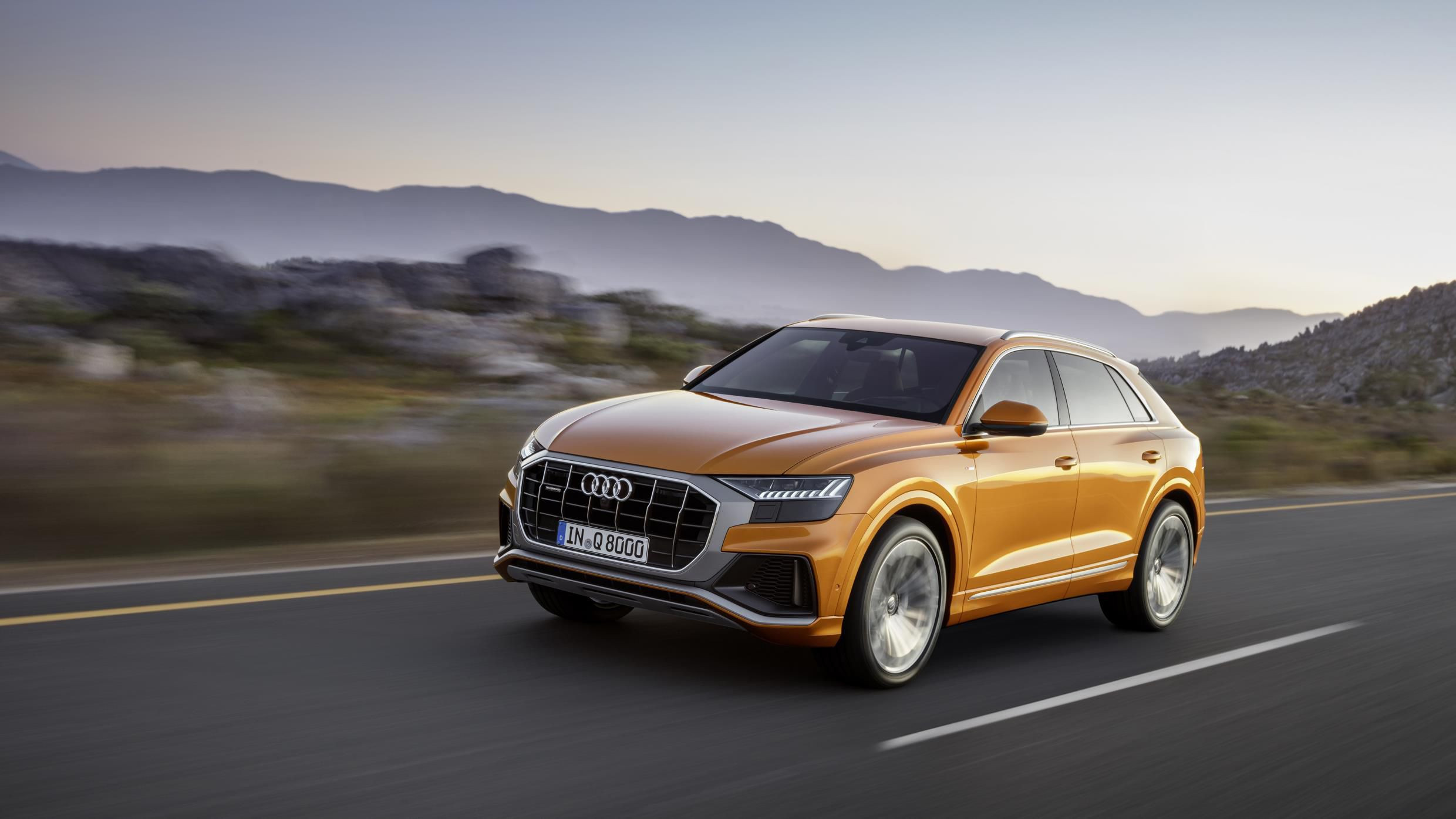 Metallic orange Audi Q8 whizzing along desert road