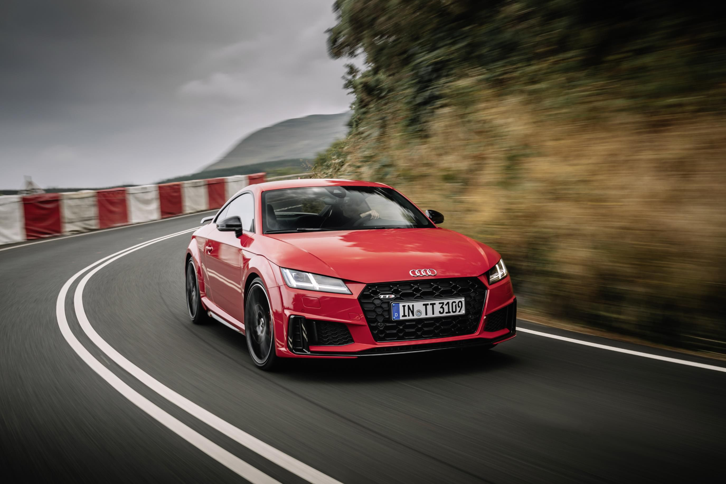 Red Audi TT taking a corner at speed