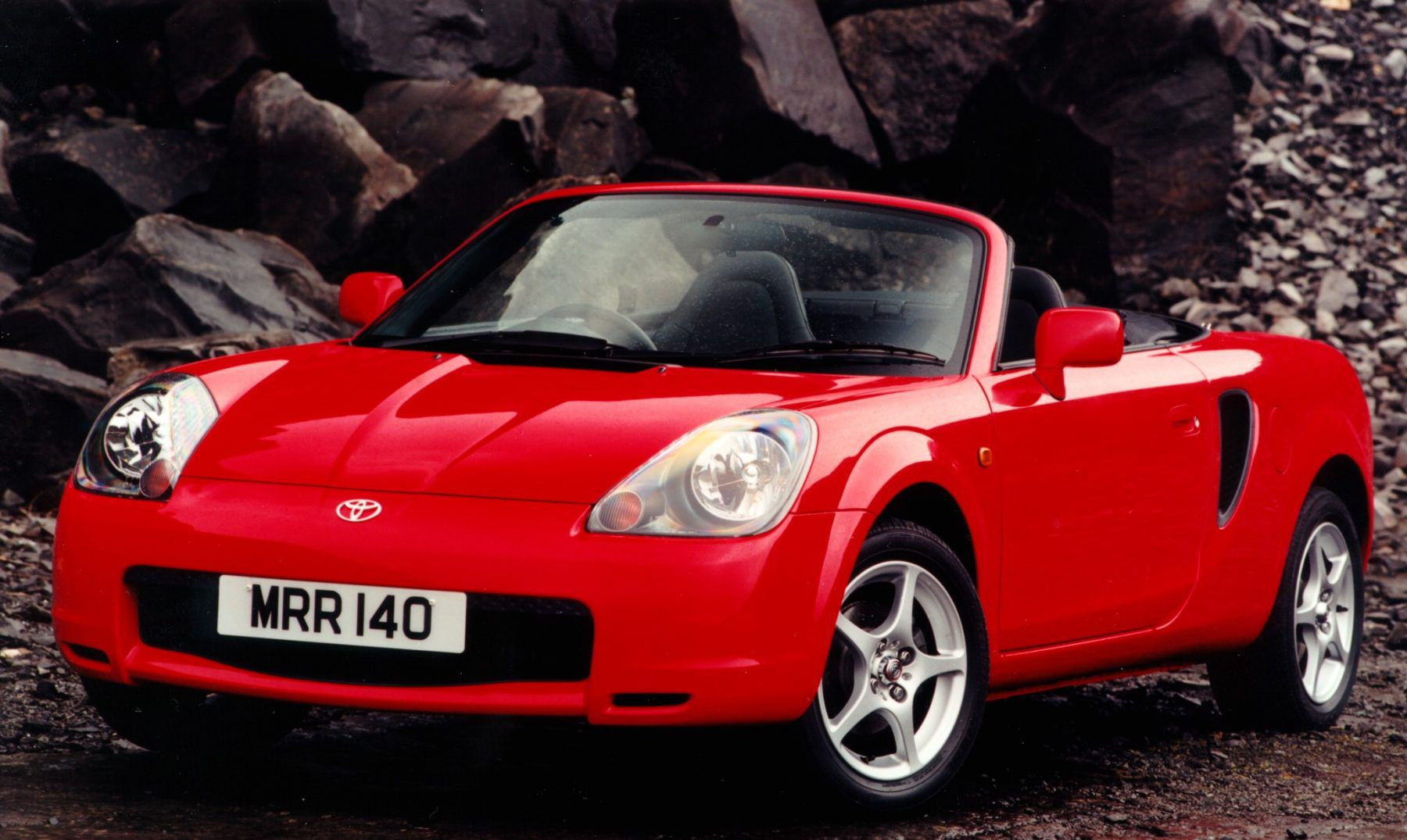 Red Toyota MR2 in front of a rock