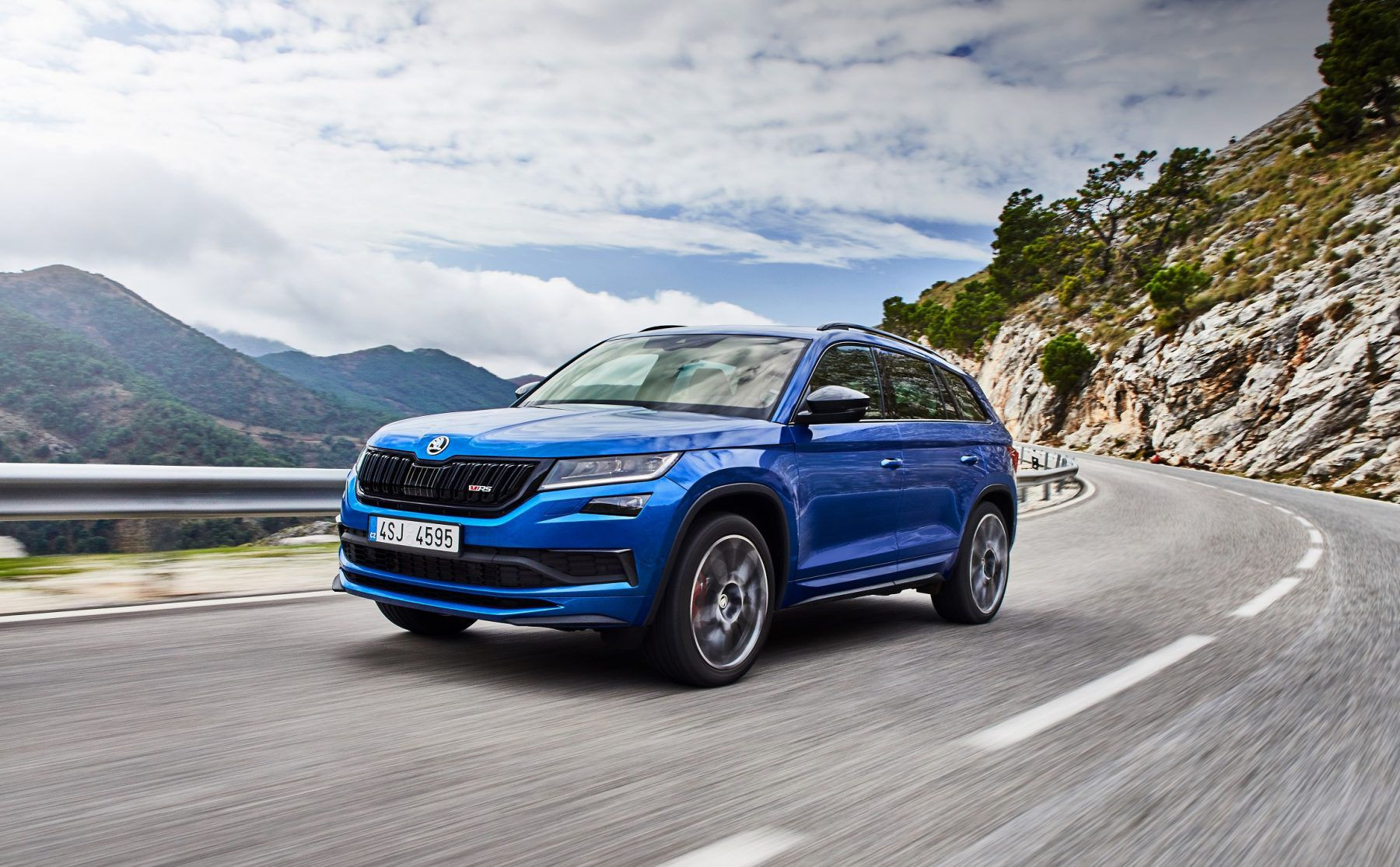 Front view of a blue Skoda Kodiaq driving on a road
