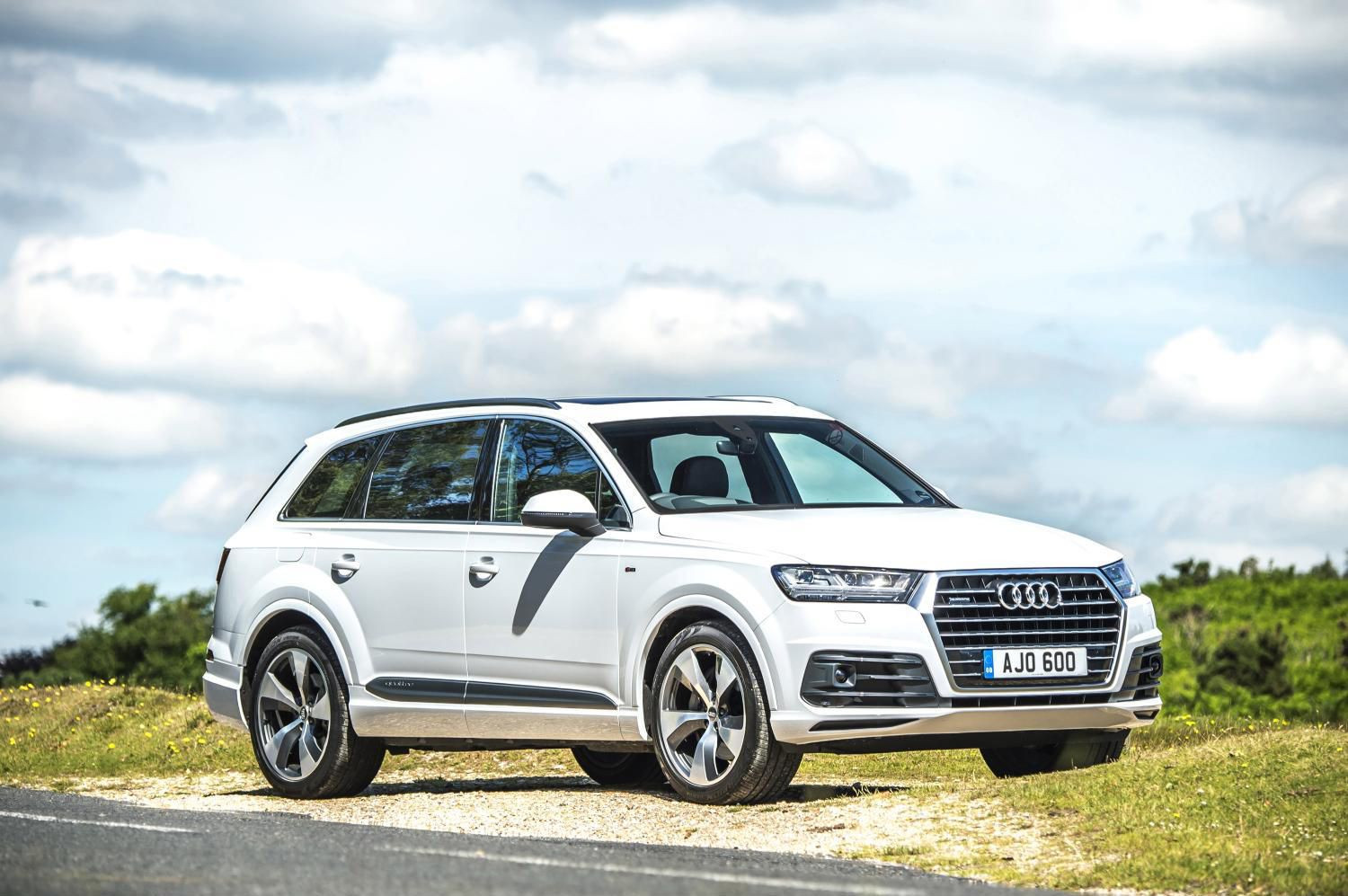 White Audi Q7 parked on grass at the side of the road, facing three-quarters right.