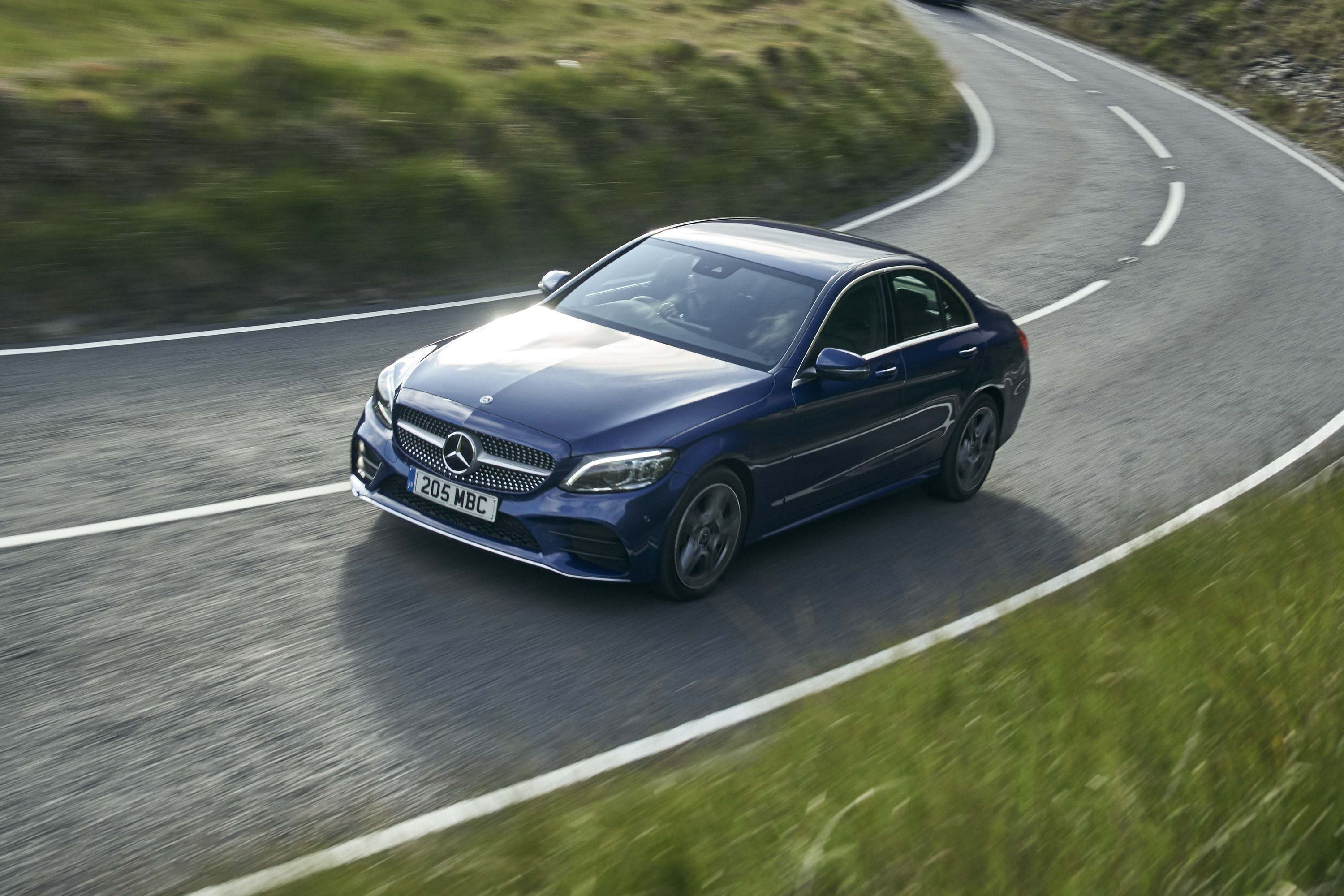 Blue Mercedes-Benz C-Class driving on a road