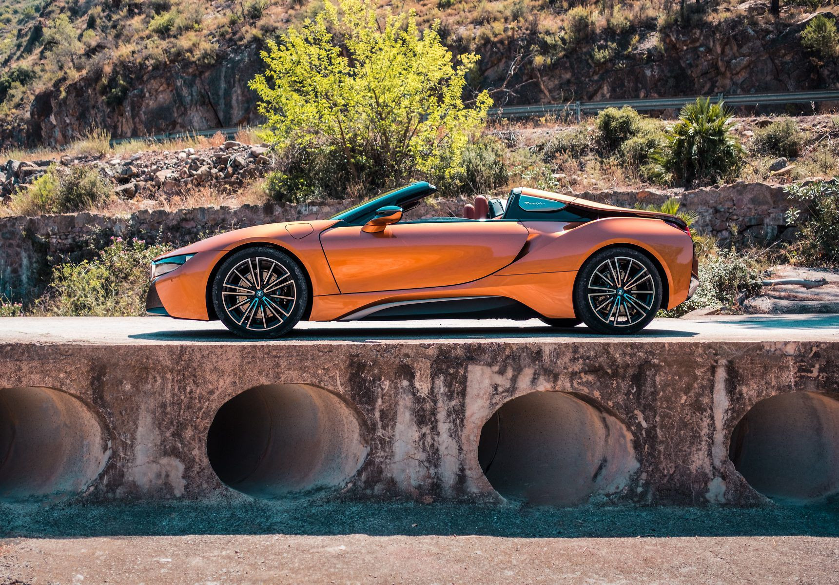 Orange BMW i8 Roadster parked in front of rocky mountain