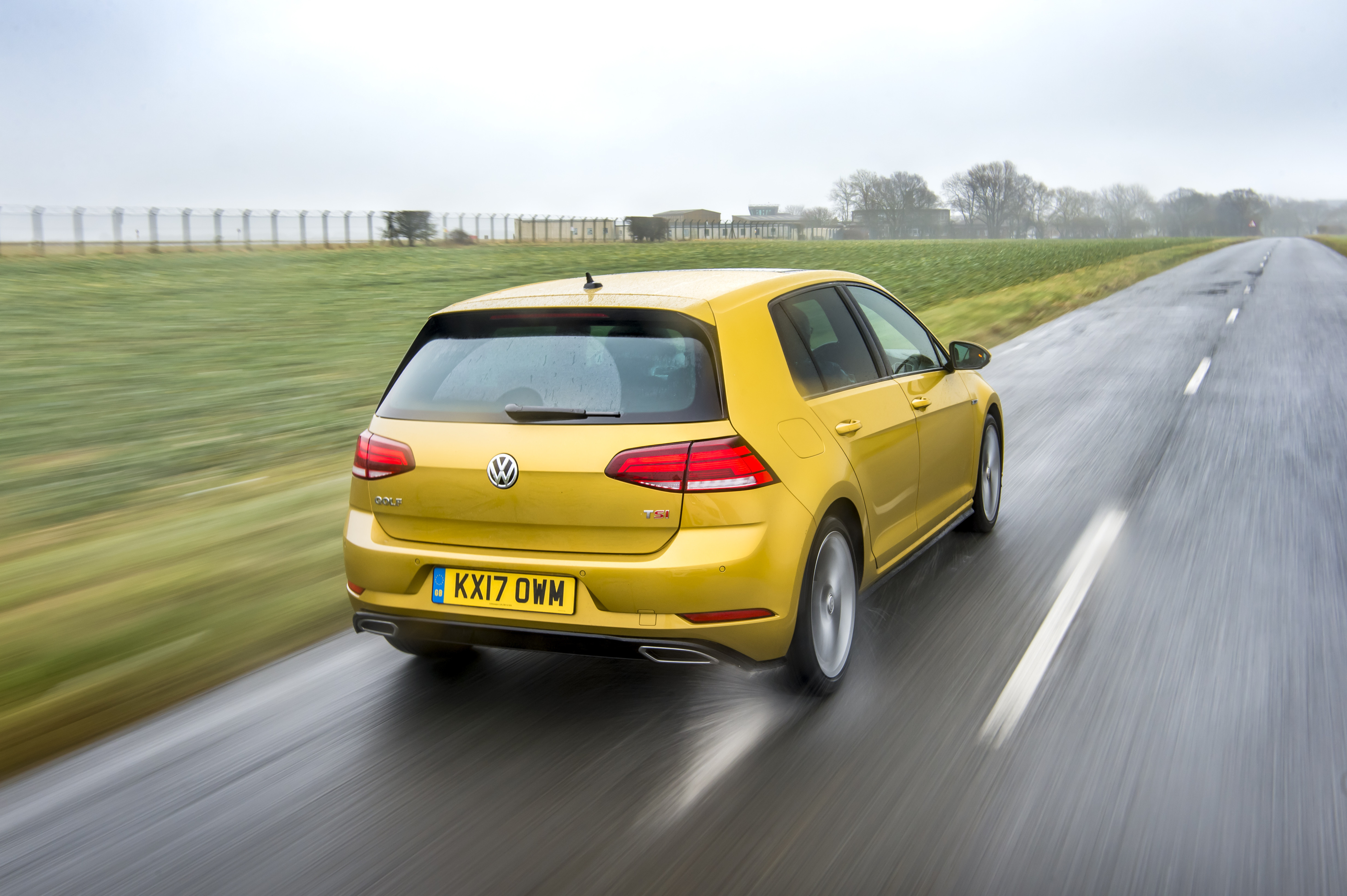 Rear view of a yellow Golf R Line driving on a road