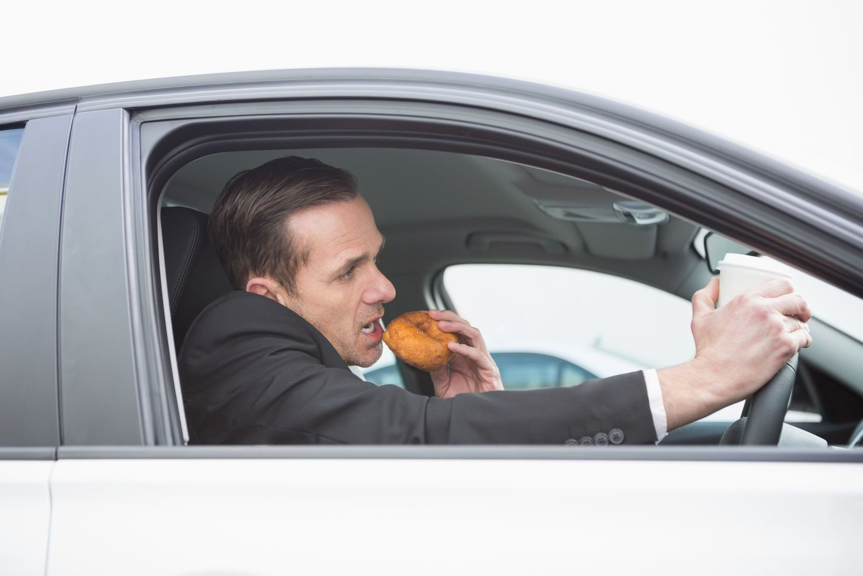 Man eating food whilst driving