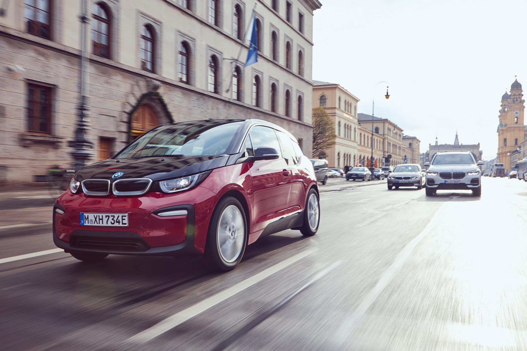 Red BMW i3s driving on a road