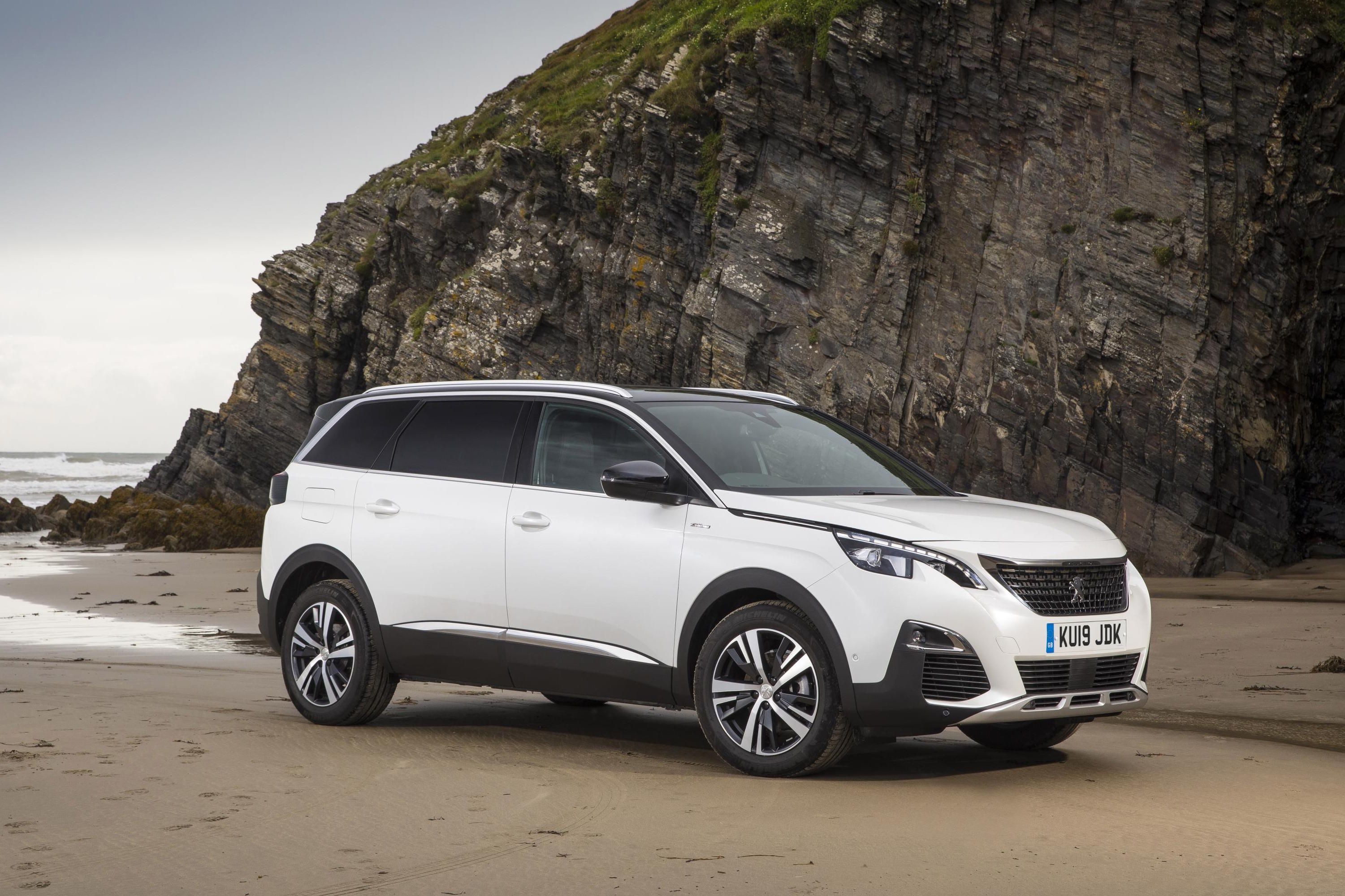 White Peugeot 5008 SUV parked on beach in front of rocky outcrop, facing three-quarters right.