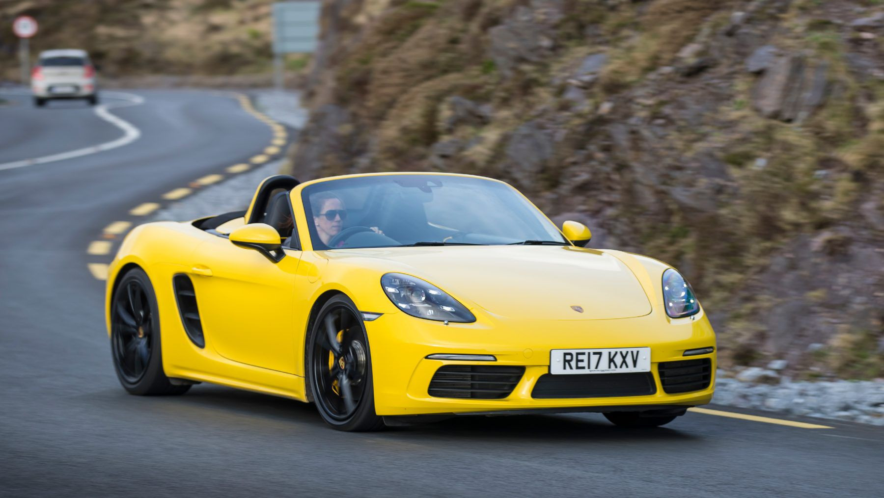 Yellow Porsche 718 Boxster driving on a road