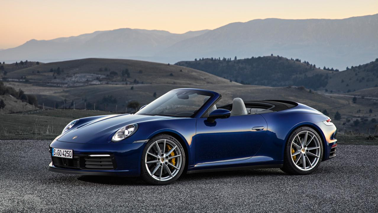 Blue Porsche 911 Cabriolet with hills and sunset in the background