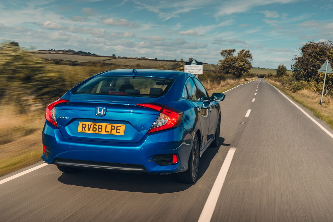 Rear view of a blue Honda Civic driving on a road