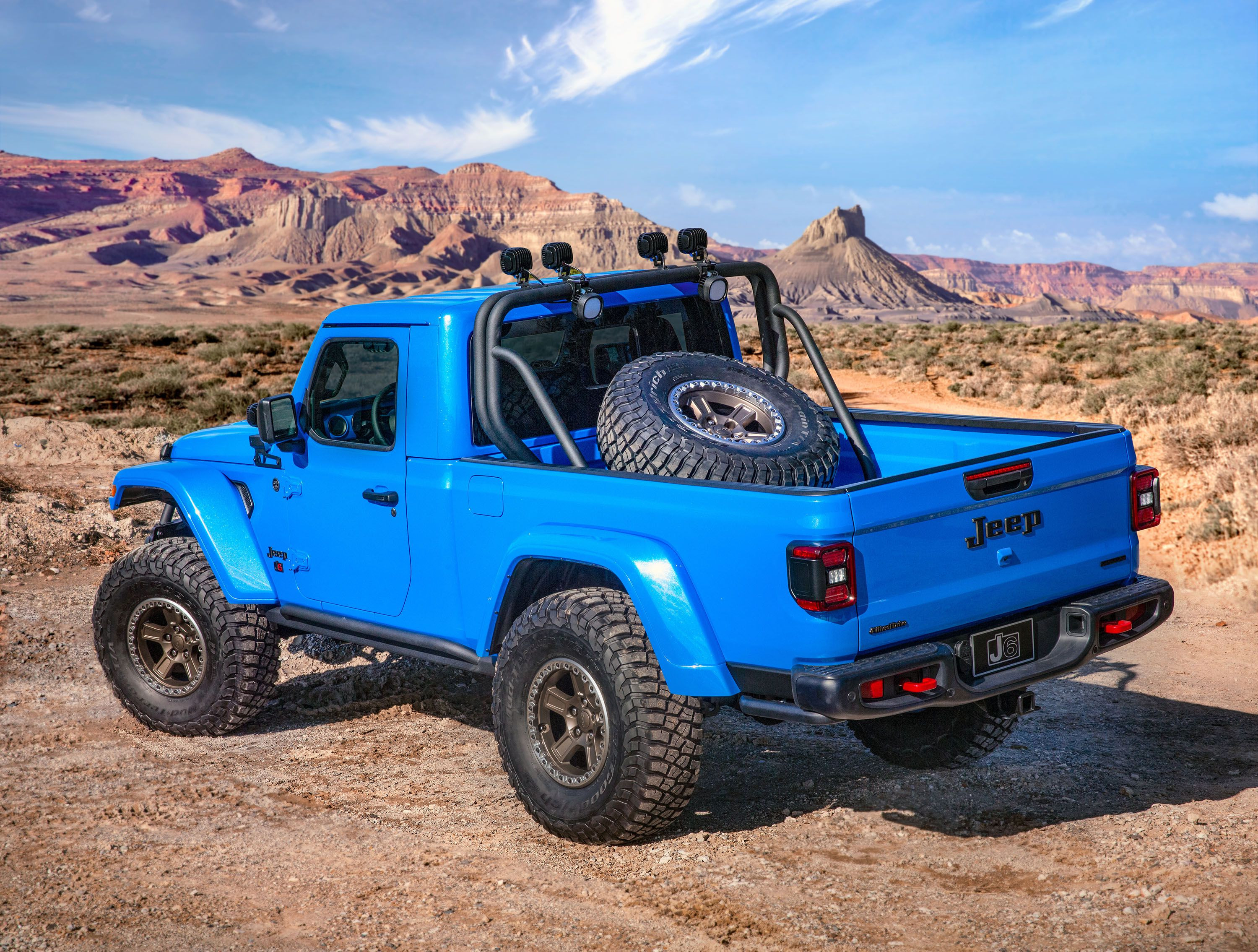 Rear view of a blue Jeep with a wheel in the trunk