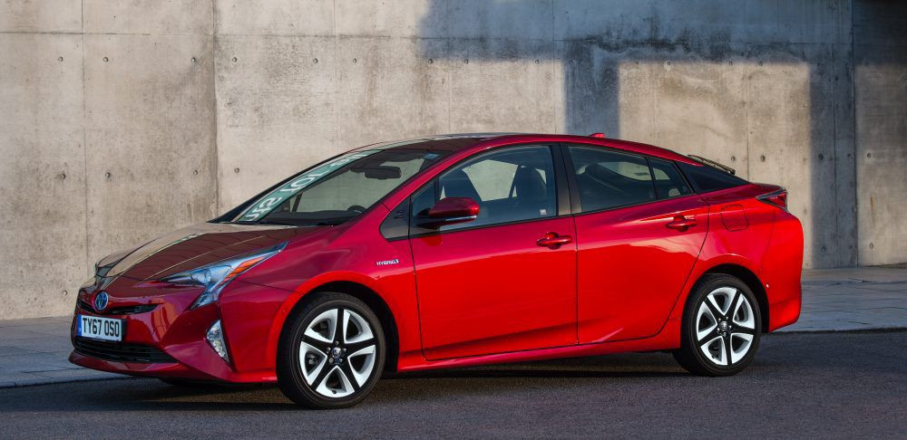 Red Toyota Prius parked in front of a wall