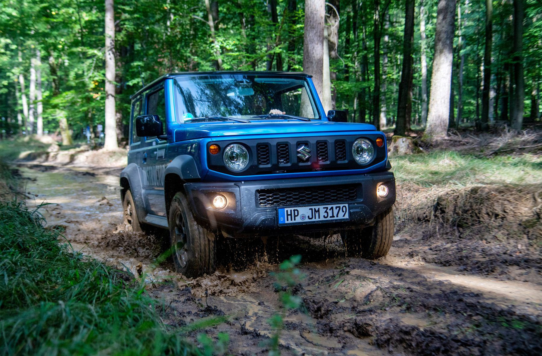 Blue Suzuki Jimny driving on mud