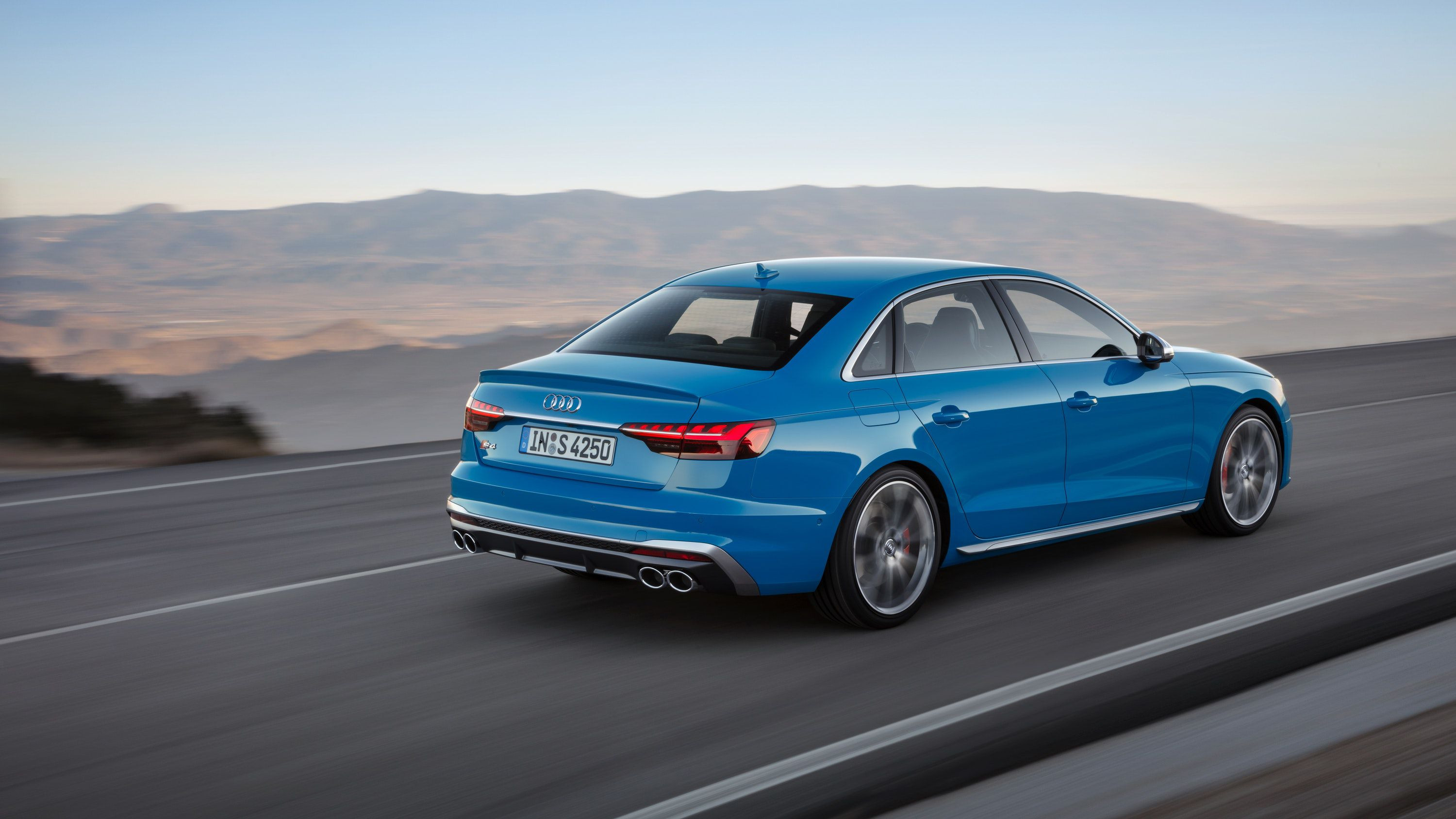 Side view of a blue Audi S4 driving on a road