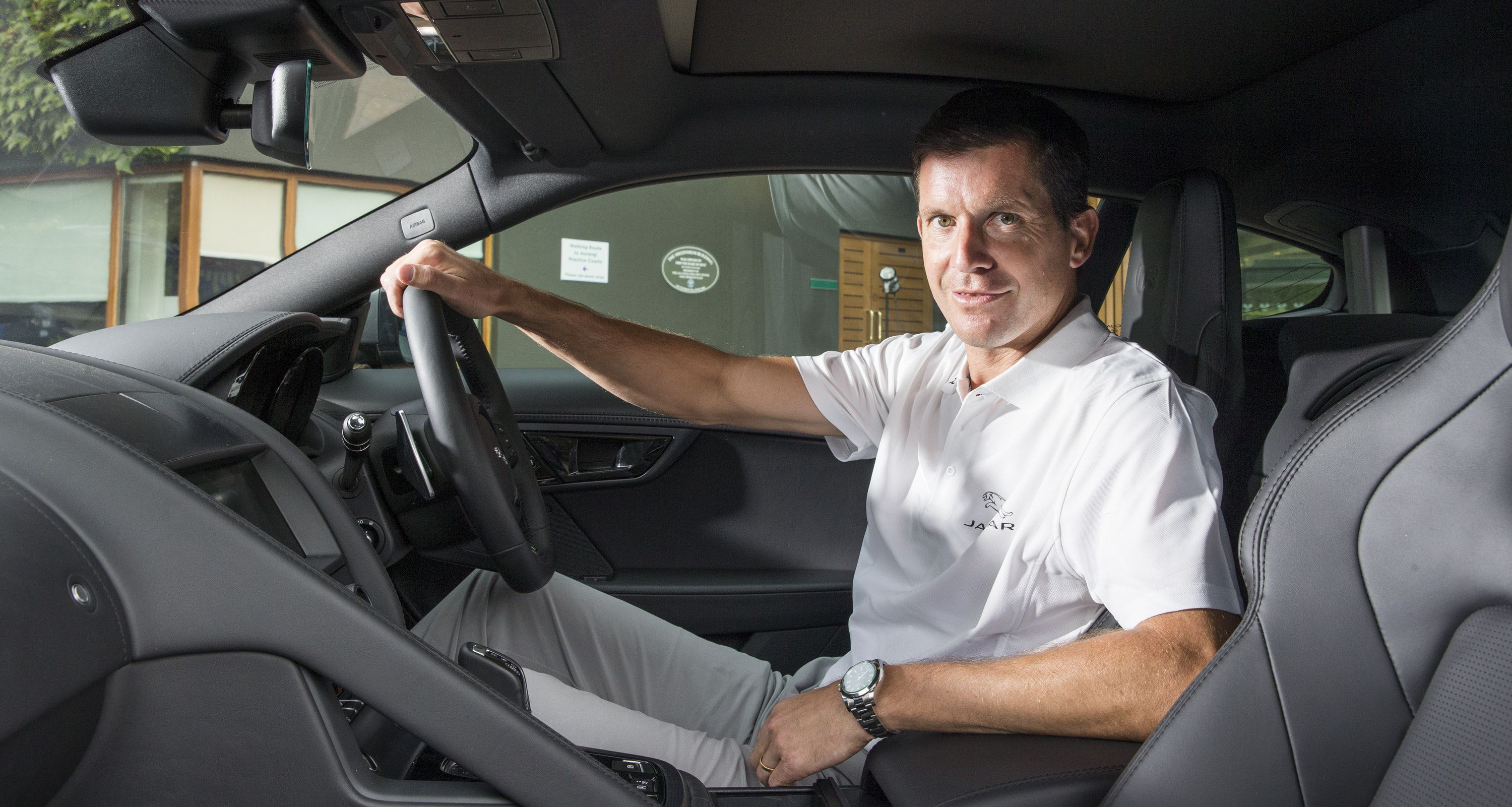 Tim Henman behind the wheel of a car