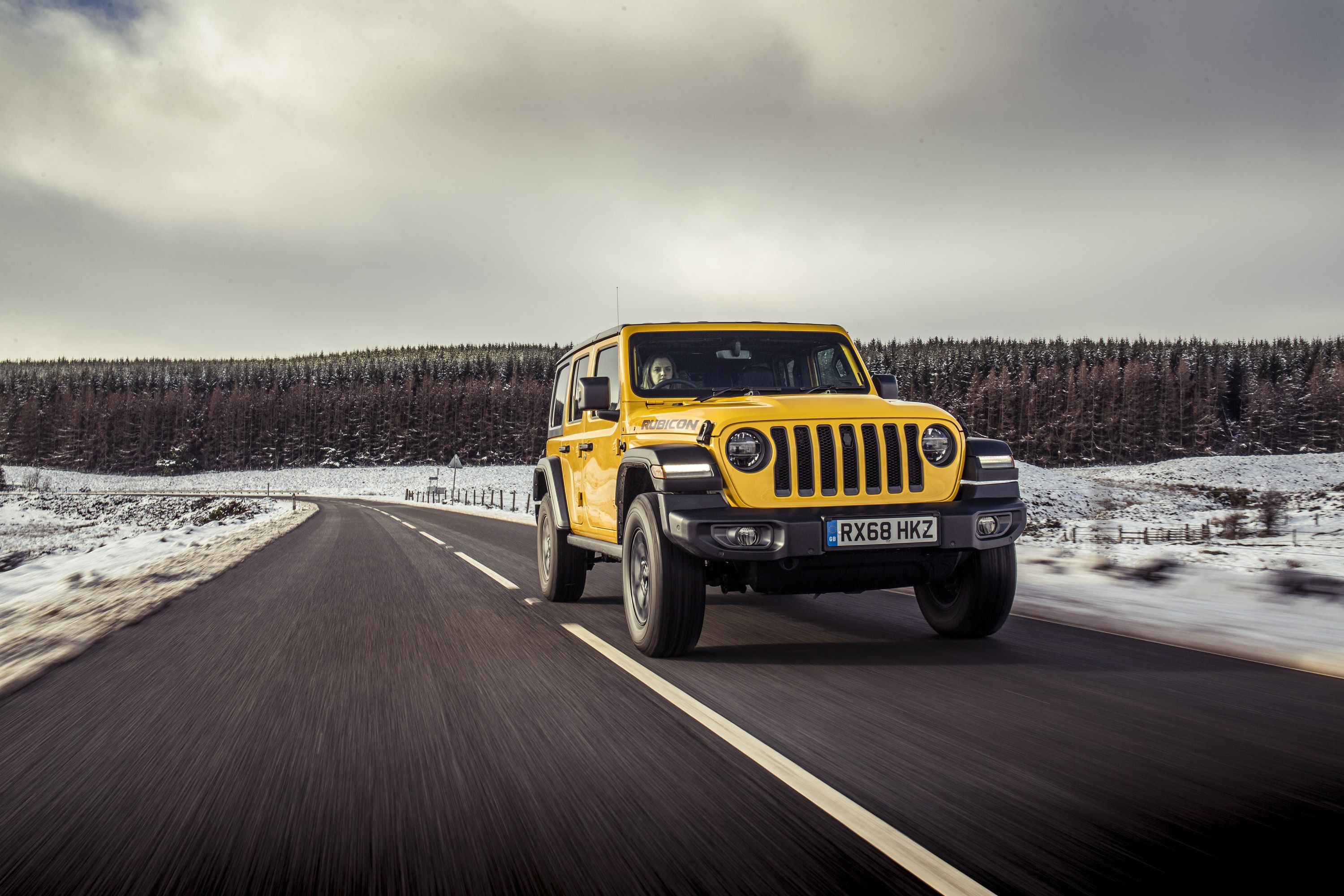 front view of yellow Jeep Wrangler driving on a road