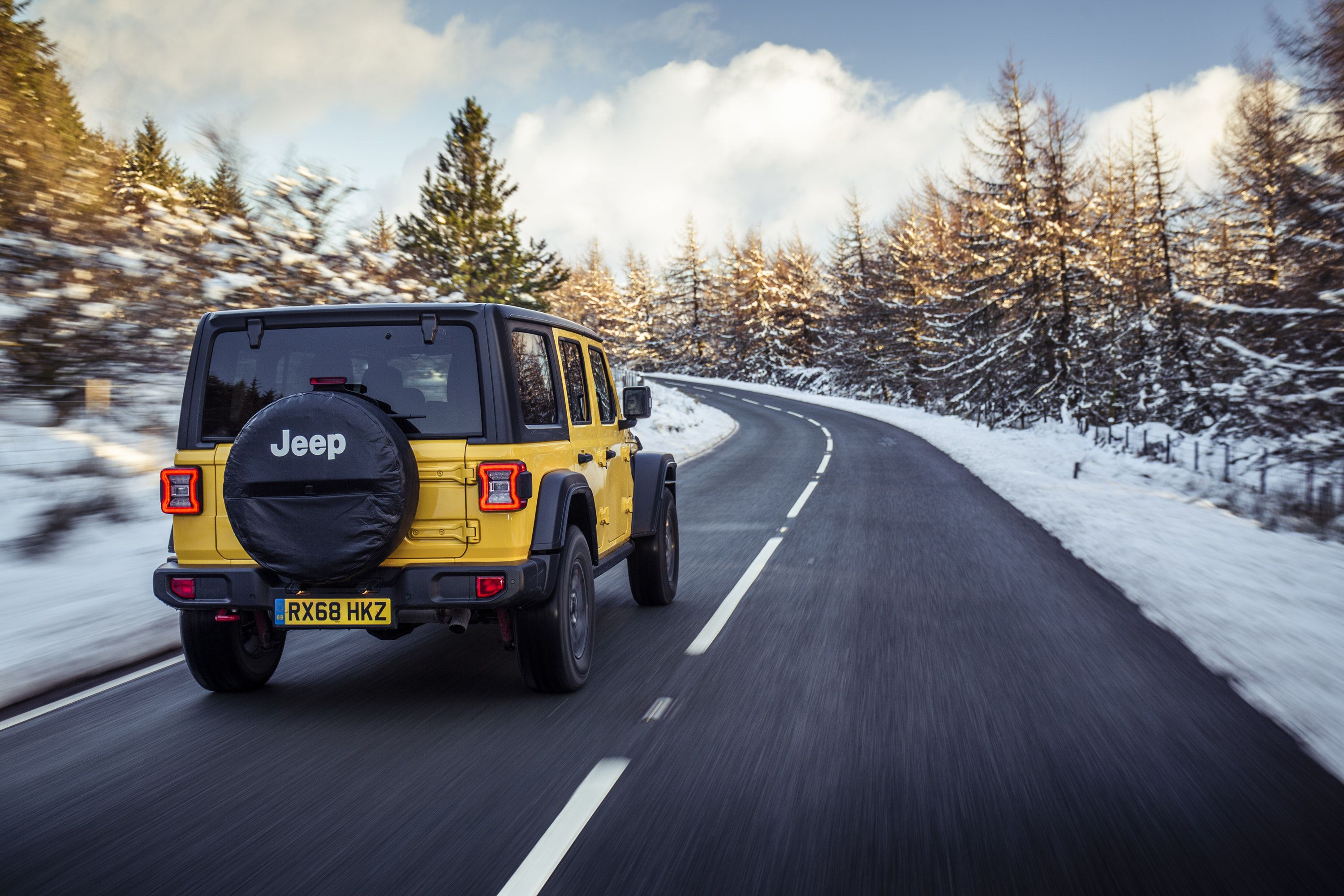 Rear view of Jeep Wrangler driving on a road