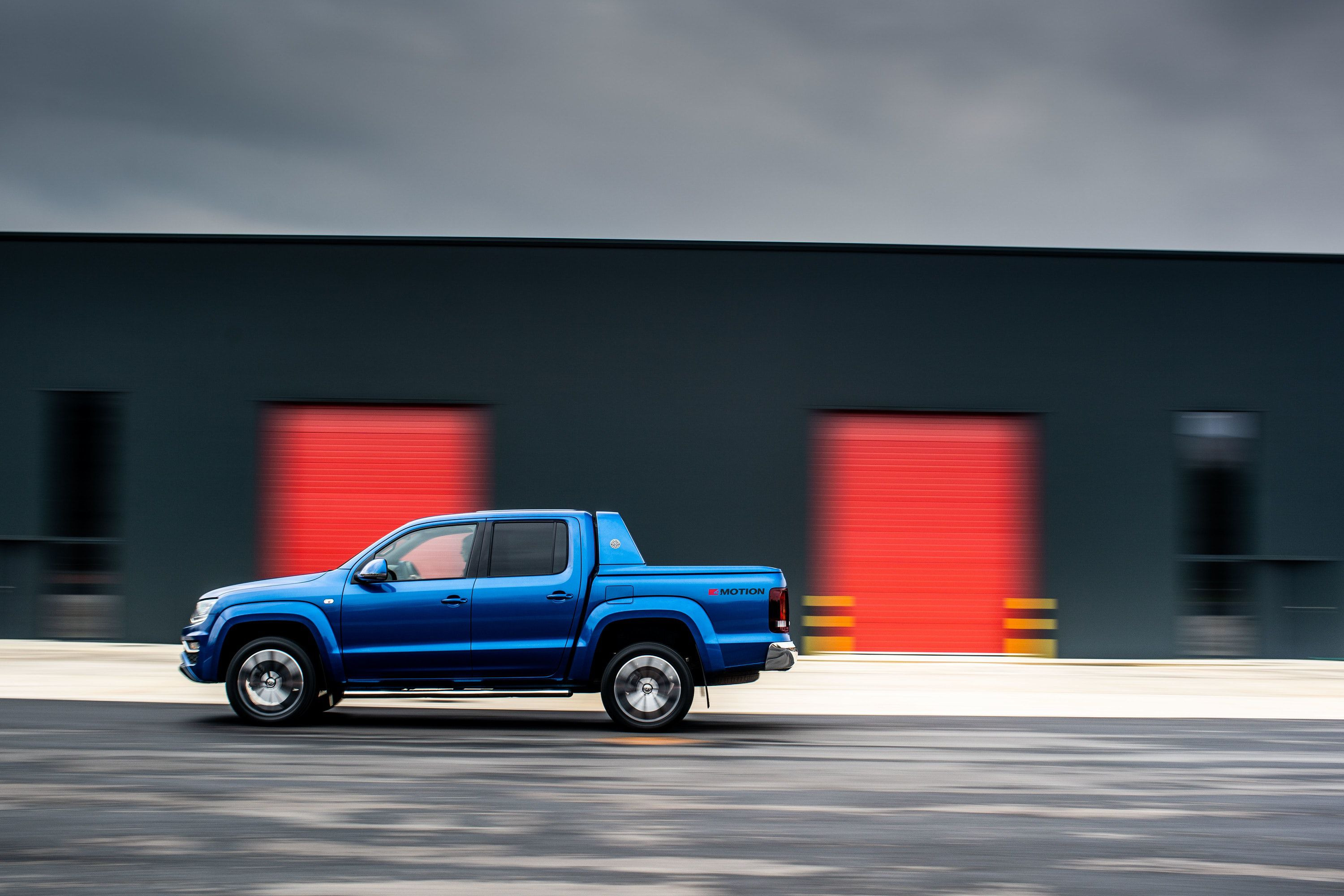 Side view of blue Amarok driving on a road