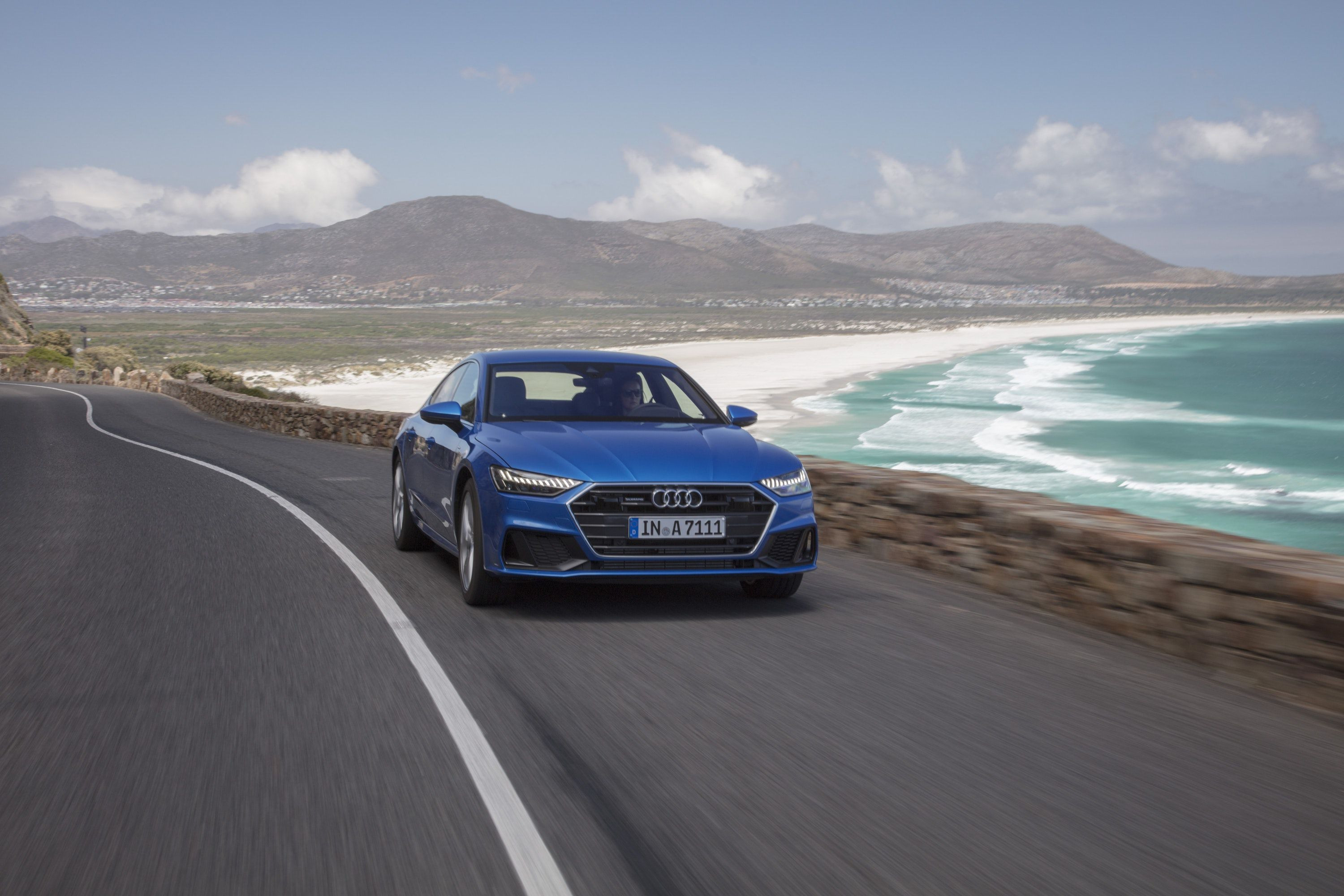 front view of a blue Audi A7 driving by the side of a beach
